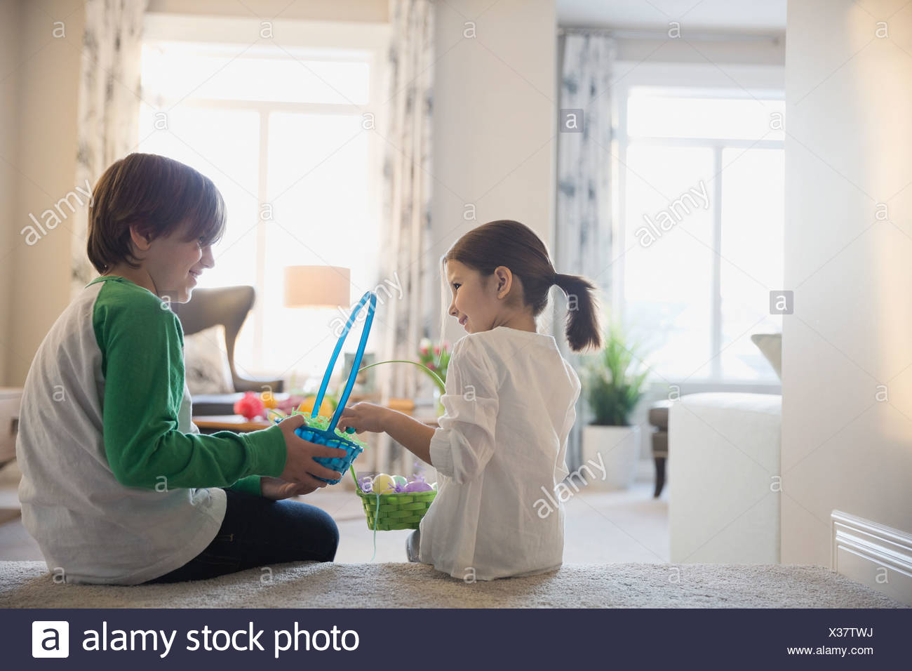 Siblings with Easter baskets at home - Stock Image