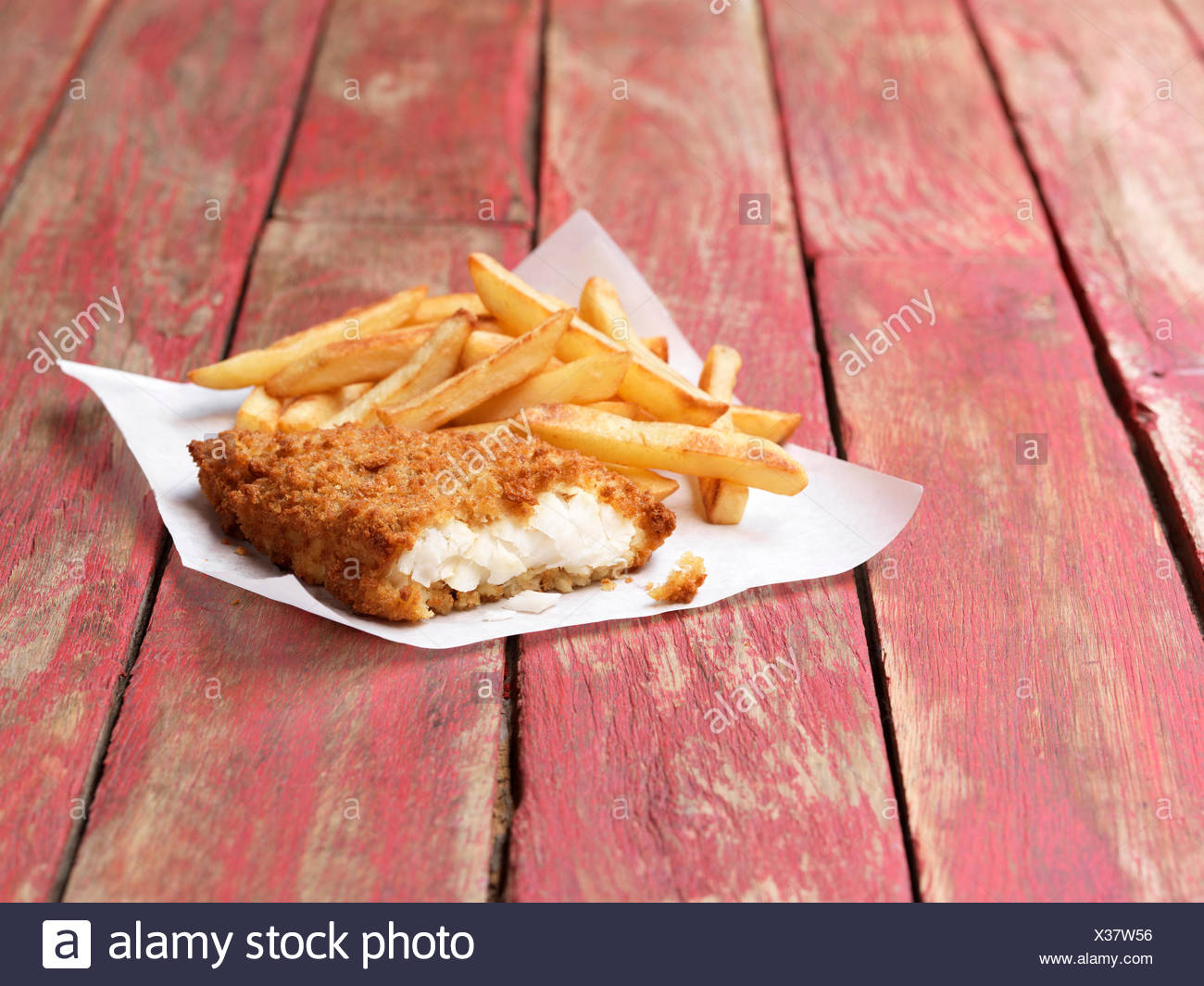 Food, fish, breaded cod and chips on rustic red painted wood - Stock Image