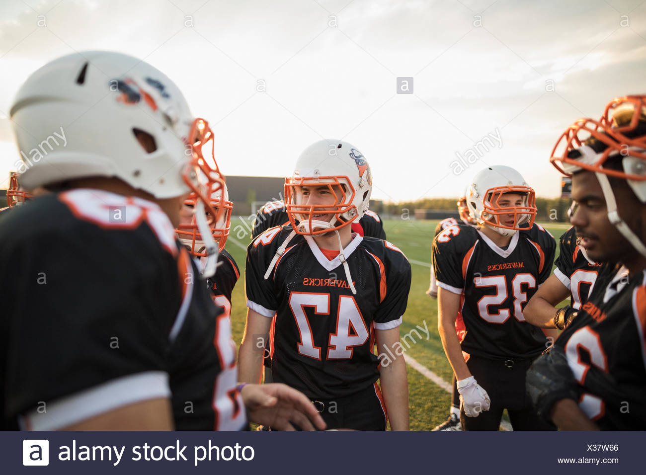 Teenage boy high school football team talking in huddle on football field - Stock Image