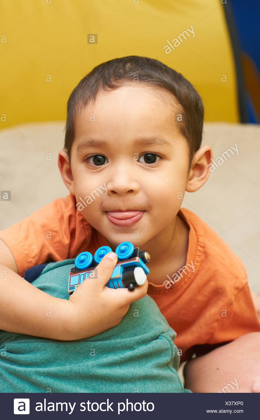 Boy playing with toy train - Stock Image