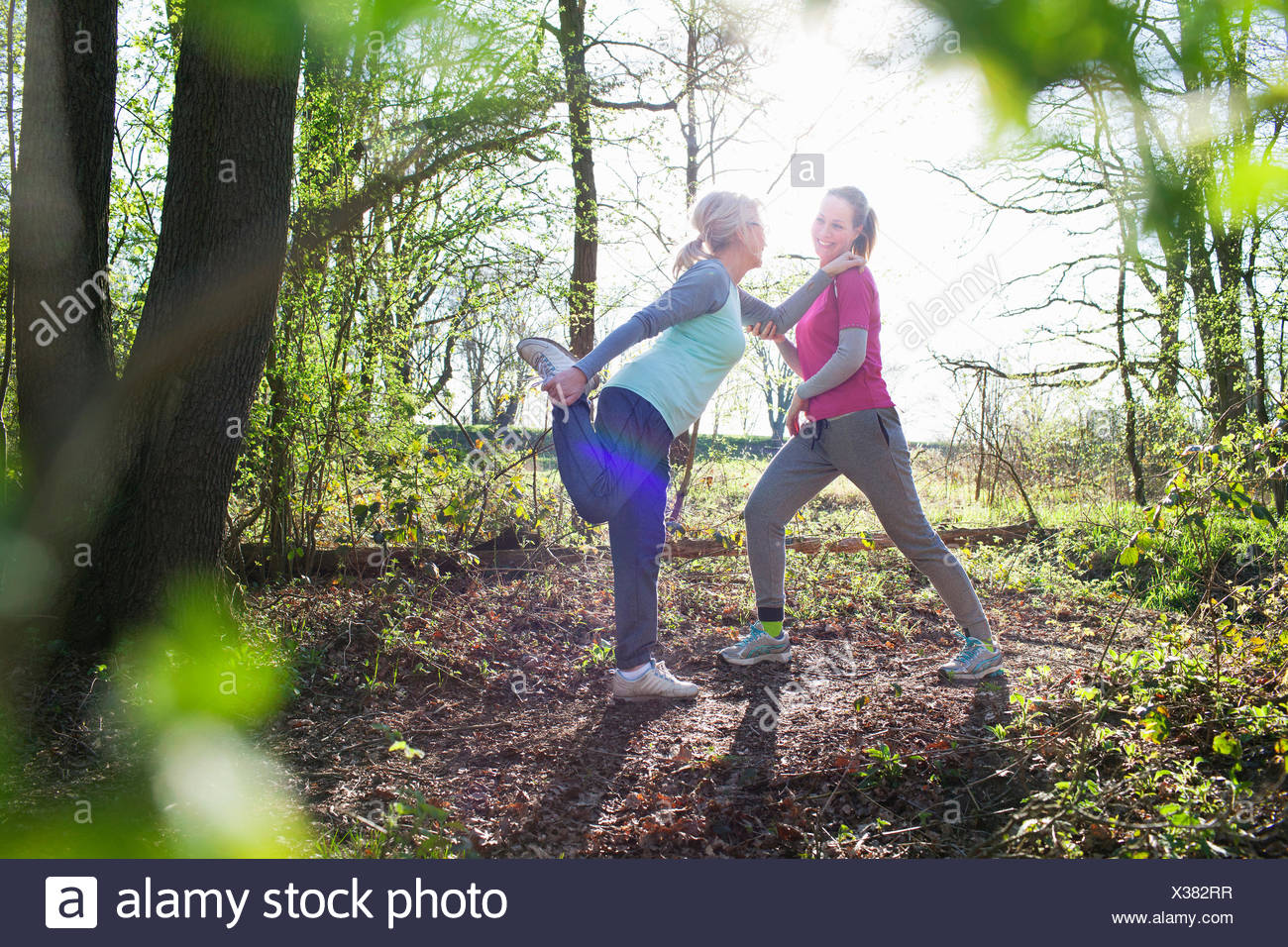 Side view of women in forest face to face holding ankle stretching leg - Stock Image