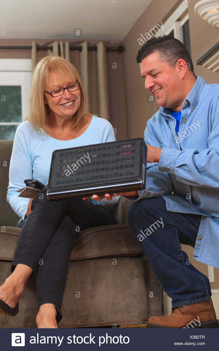 Service man showing homeowner how to use the cable box - Stock Image