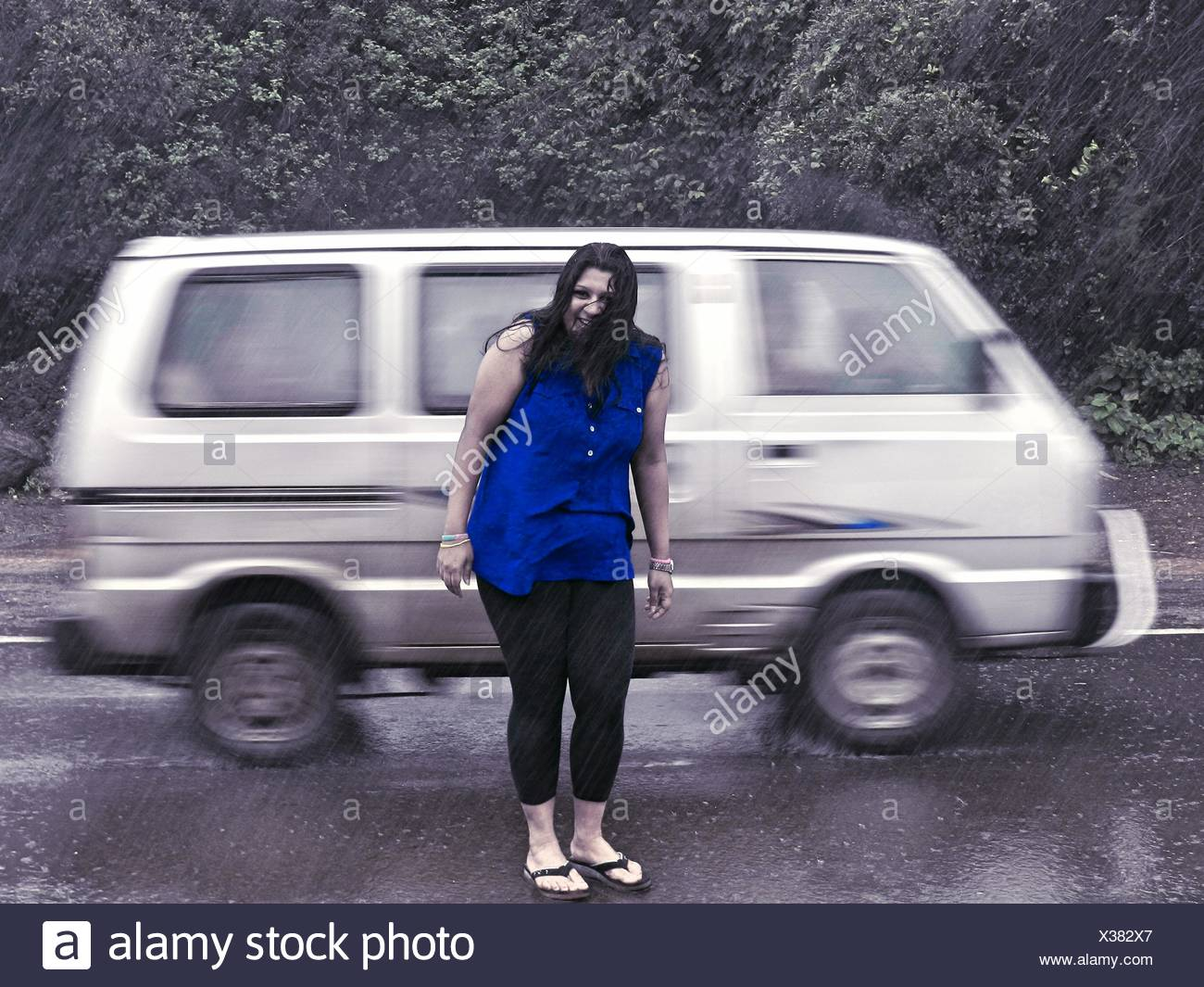 Full Length Portrait Of Woman Standing In Front Of Speeding Car On Rainy Day - Stock Image