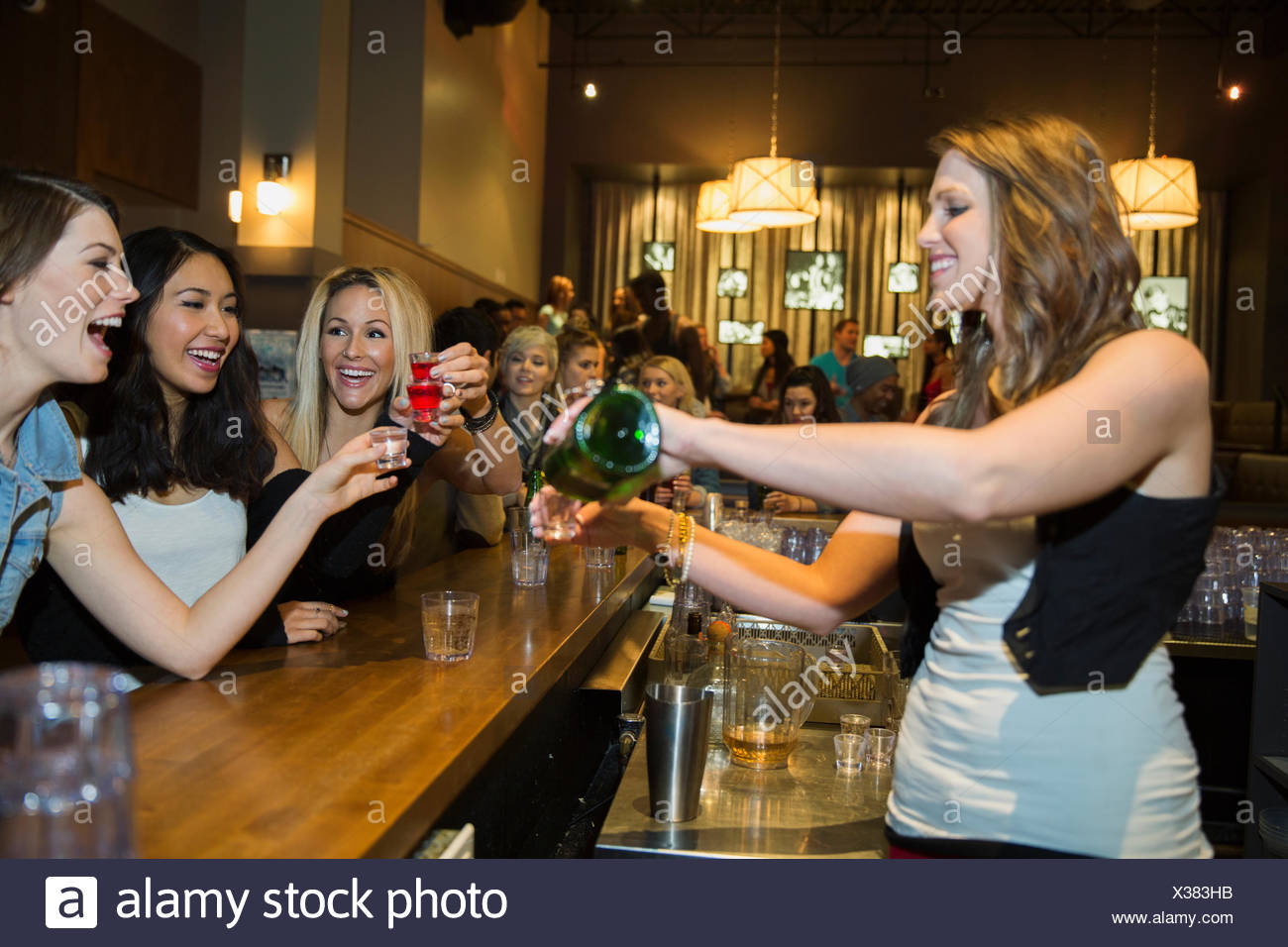 Bartender pouring shots for women at bar - Stock Image