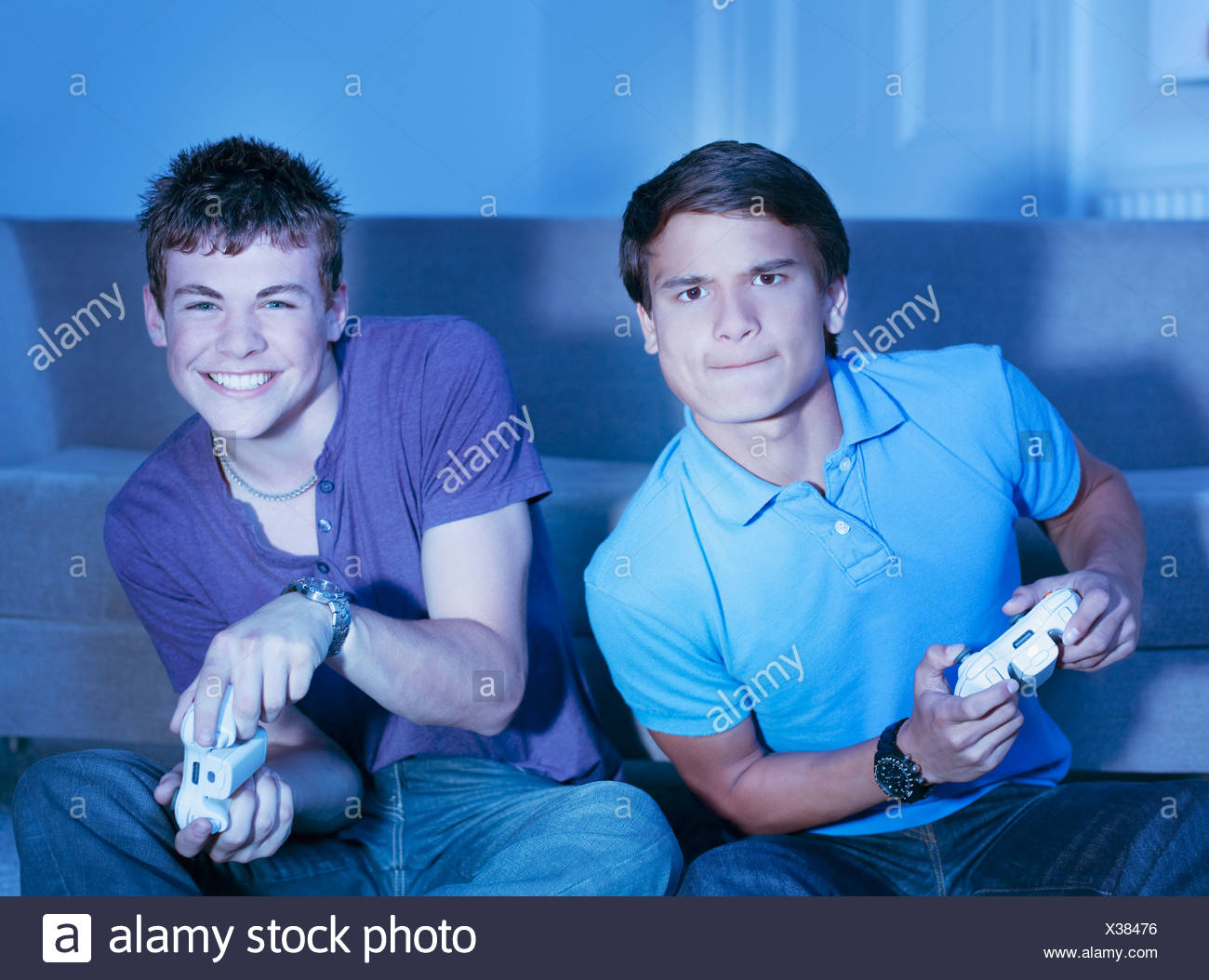Smiling teenage boys playing video game - Stock Image