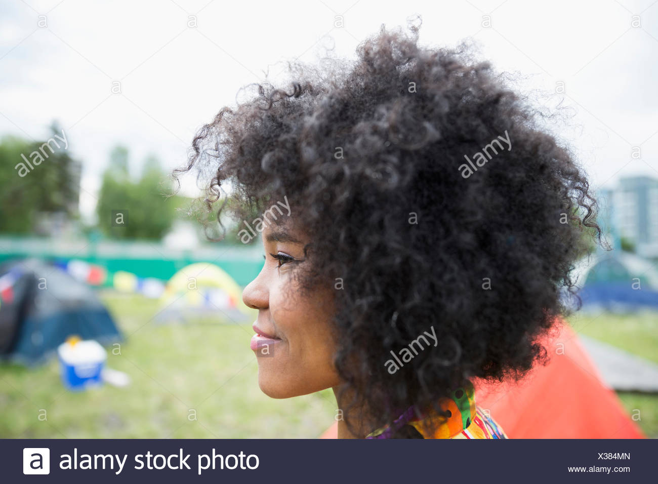 Profile portrait young woman with curly black afro looking away at summer music festival campsite - Stock Image