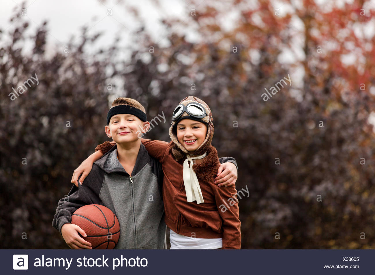 portrait of girl and twin brother wearing basketball player and