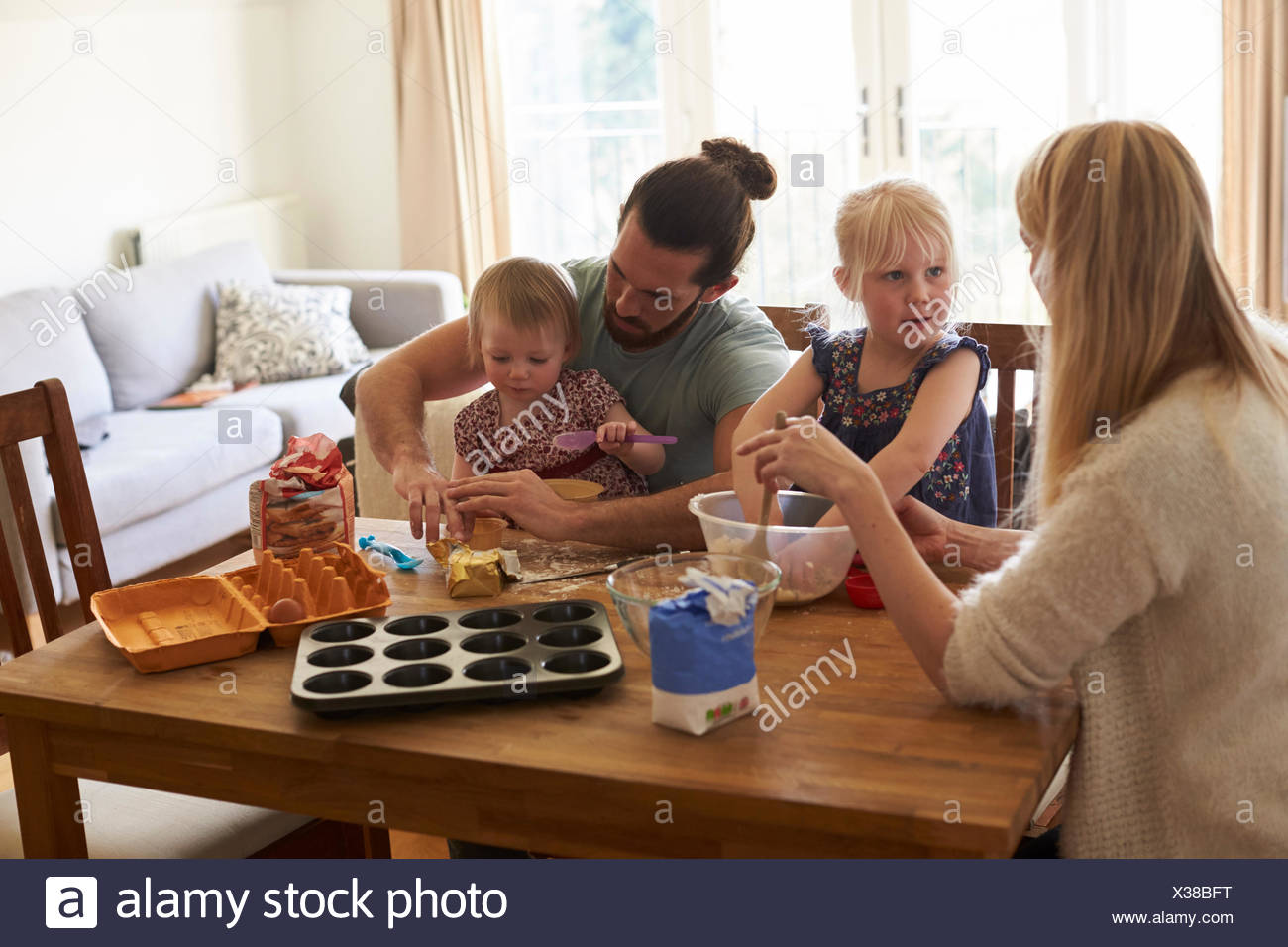 Family At Home Baking Cakes Together - Stock Image