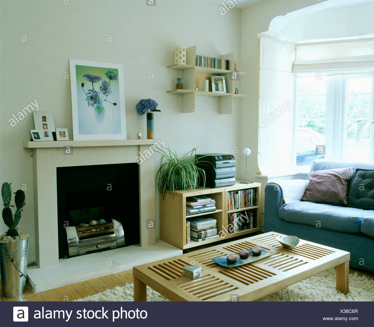 Small Wall Shelves Above Low Pale Wood Shelf Unit With Music Centre In Modern White Living Room With Simple Coffee Table Stock Photo Alamy