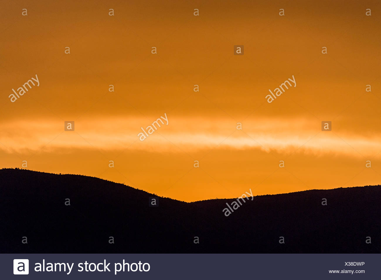 An orange sunset afterglow over a silhouette of a mountain ridge line. - Stock Image
