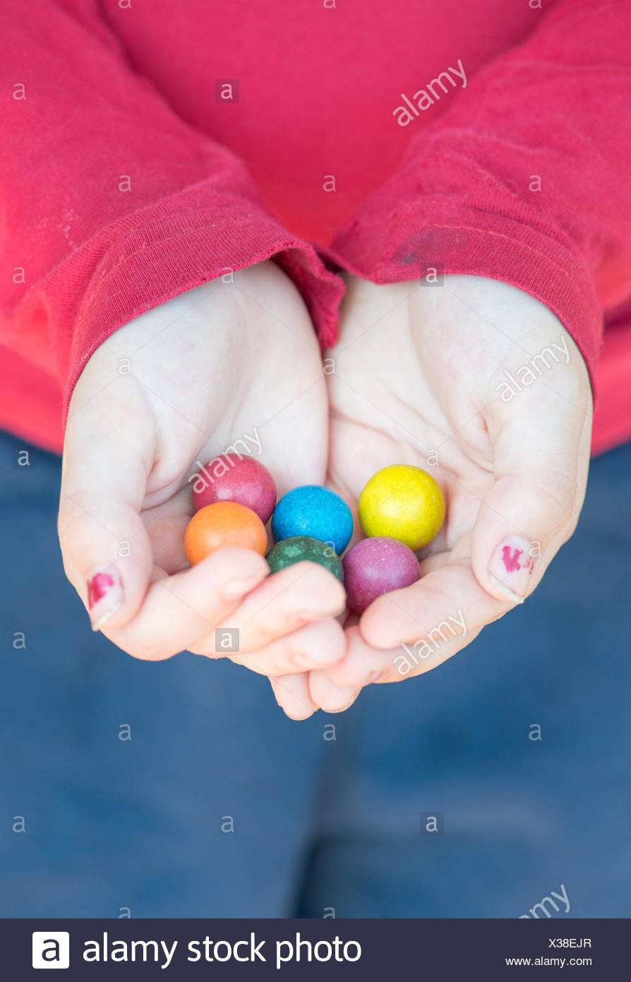 Childhood moment. Hands of child holding colorful toy marbles. - Stock Image
