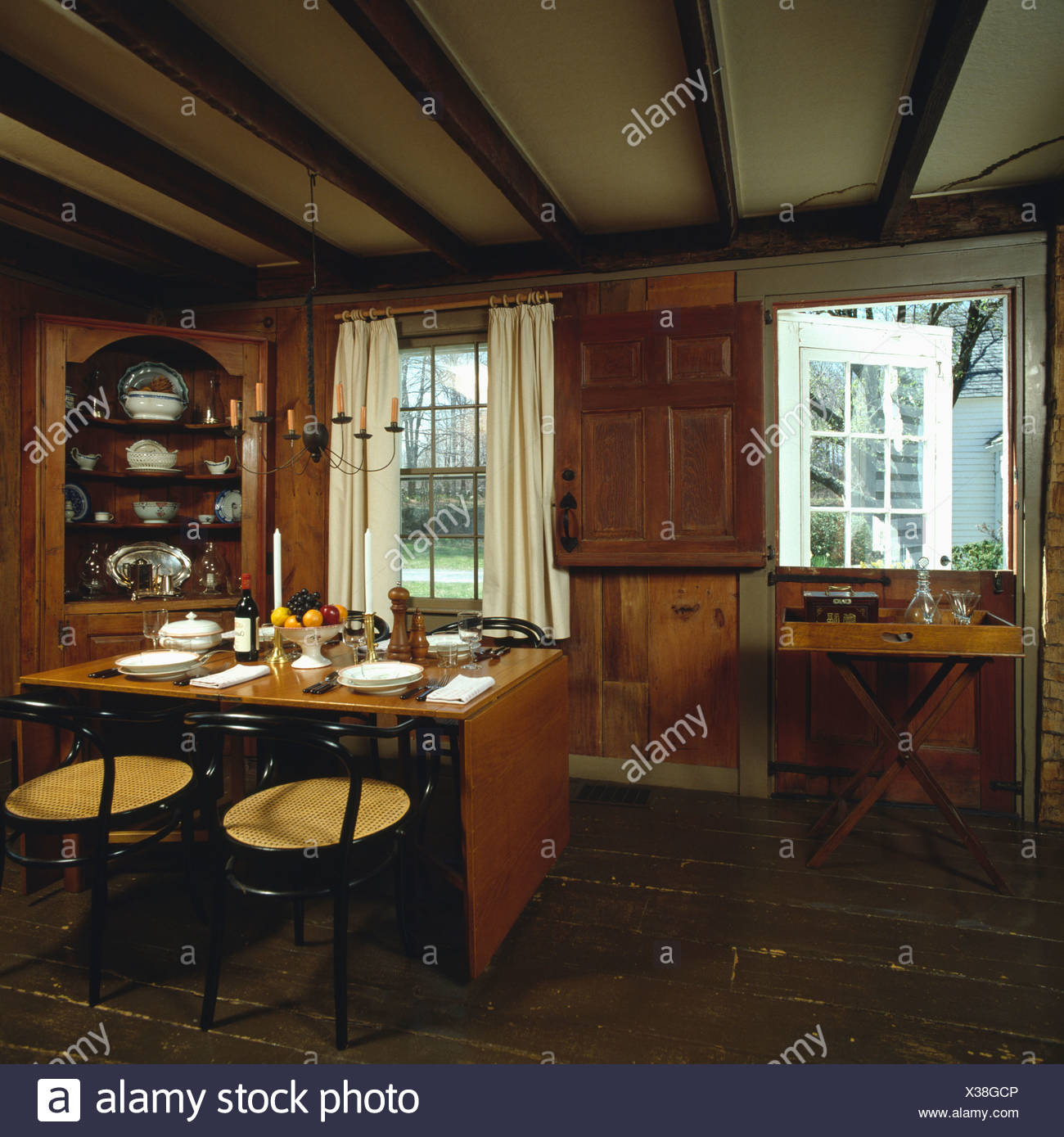Small panelled country diningroom with corner cupboard and small table - Stock Image