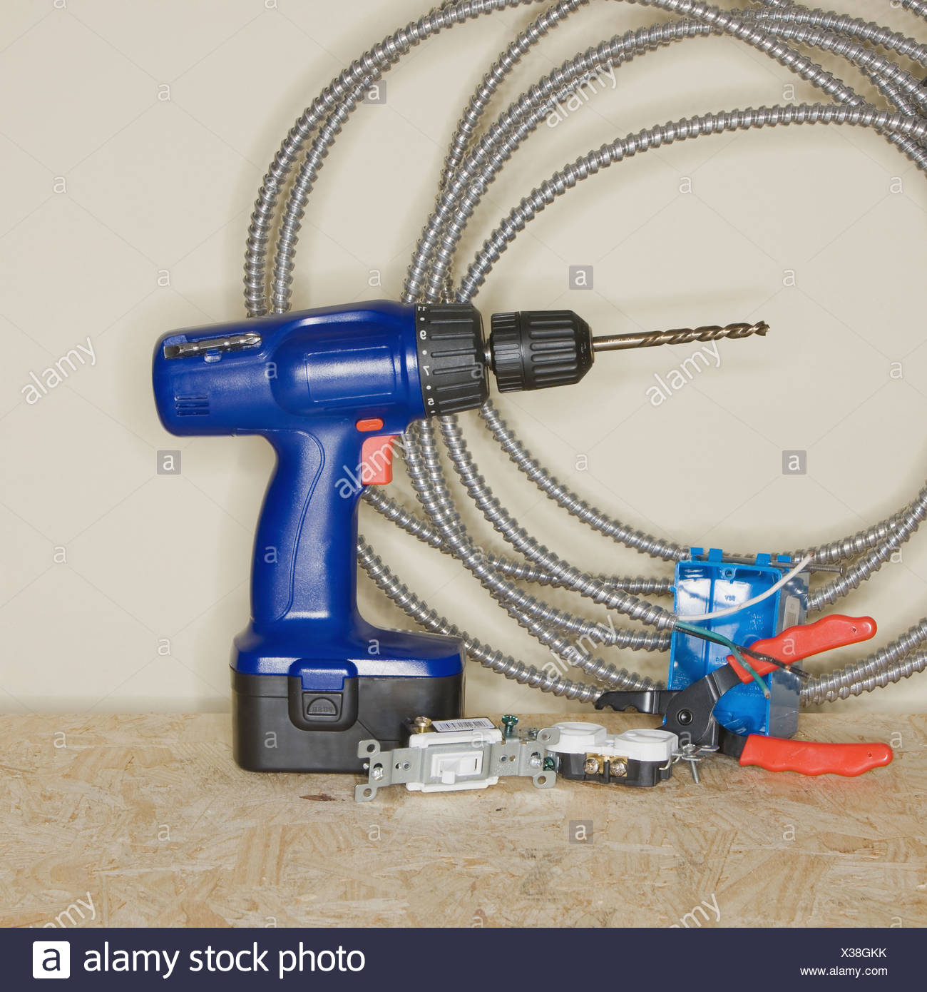Cordless drill next to wire cutters and cable - Stock Image