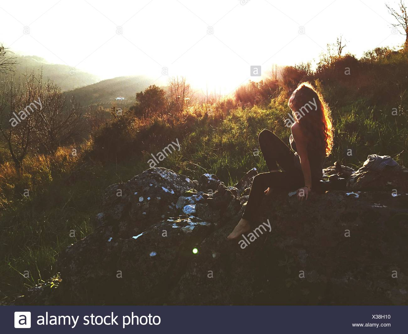 Side-View Of Young Woman Sitting On Rock Stock Photo