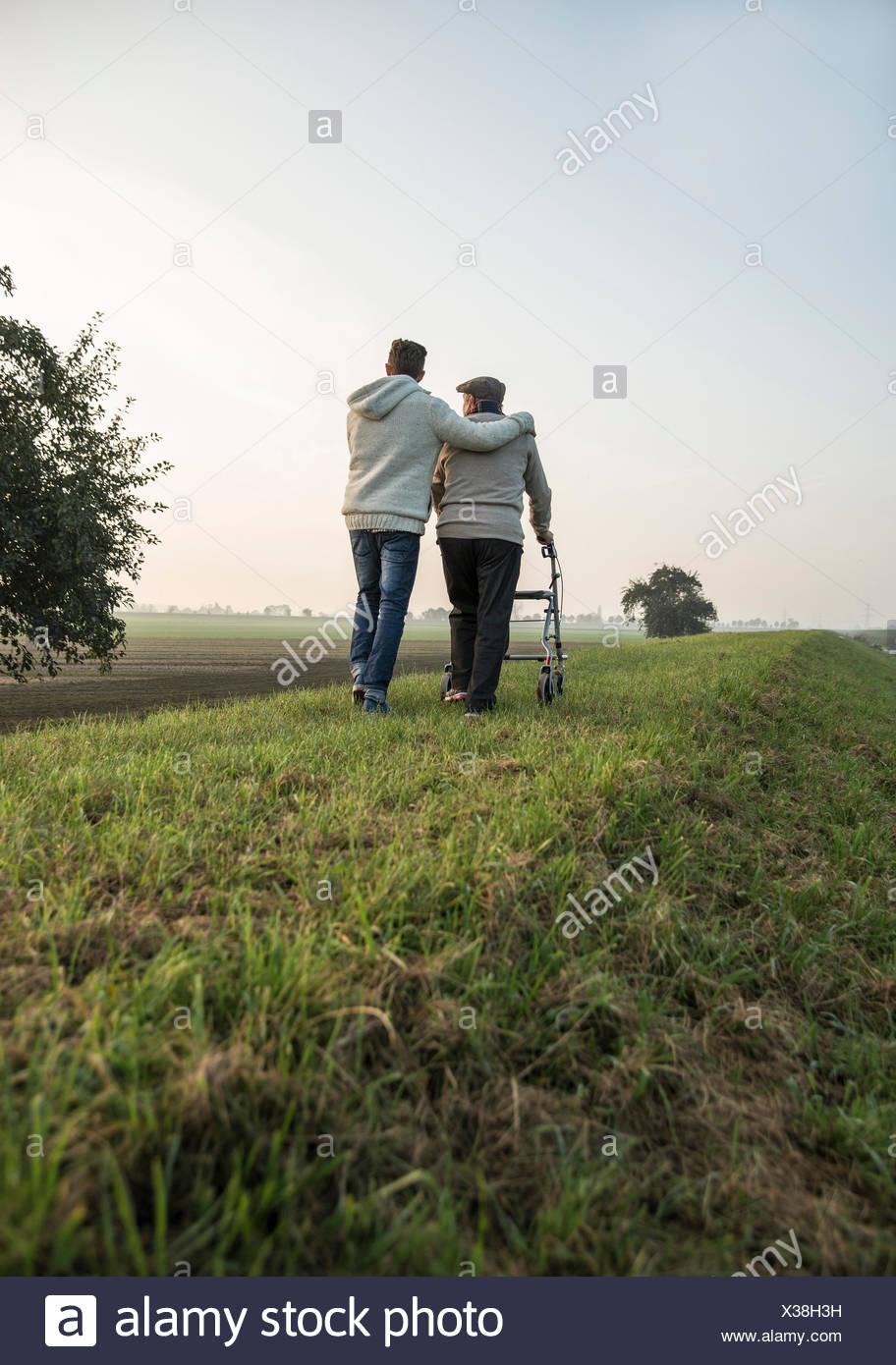 Senior man and grandson in rural landscape with wheeled walker - Stock Image