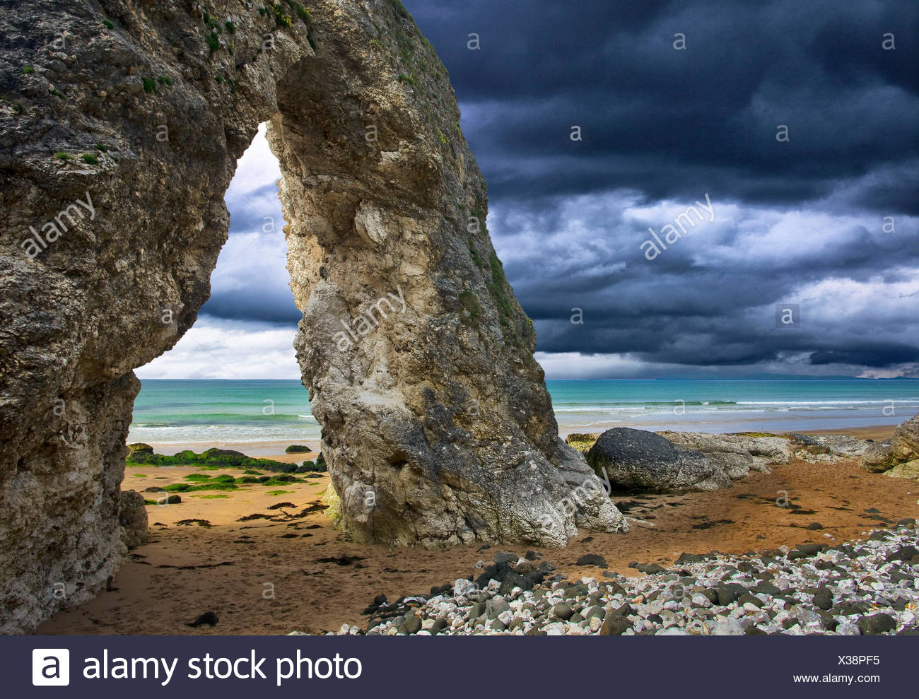 Northern Ireland, Antrim, Bushmills, rock gate on the Causeway Coast, front carrying rain over the sea - Stock Image