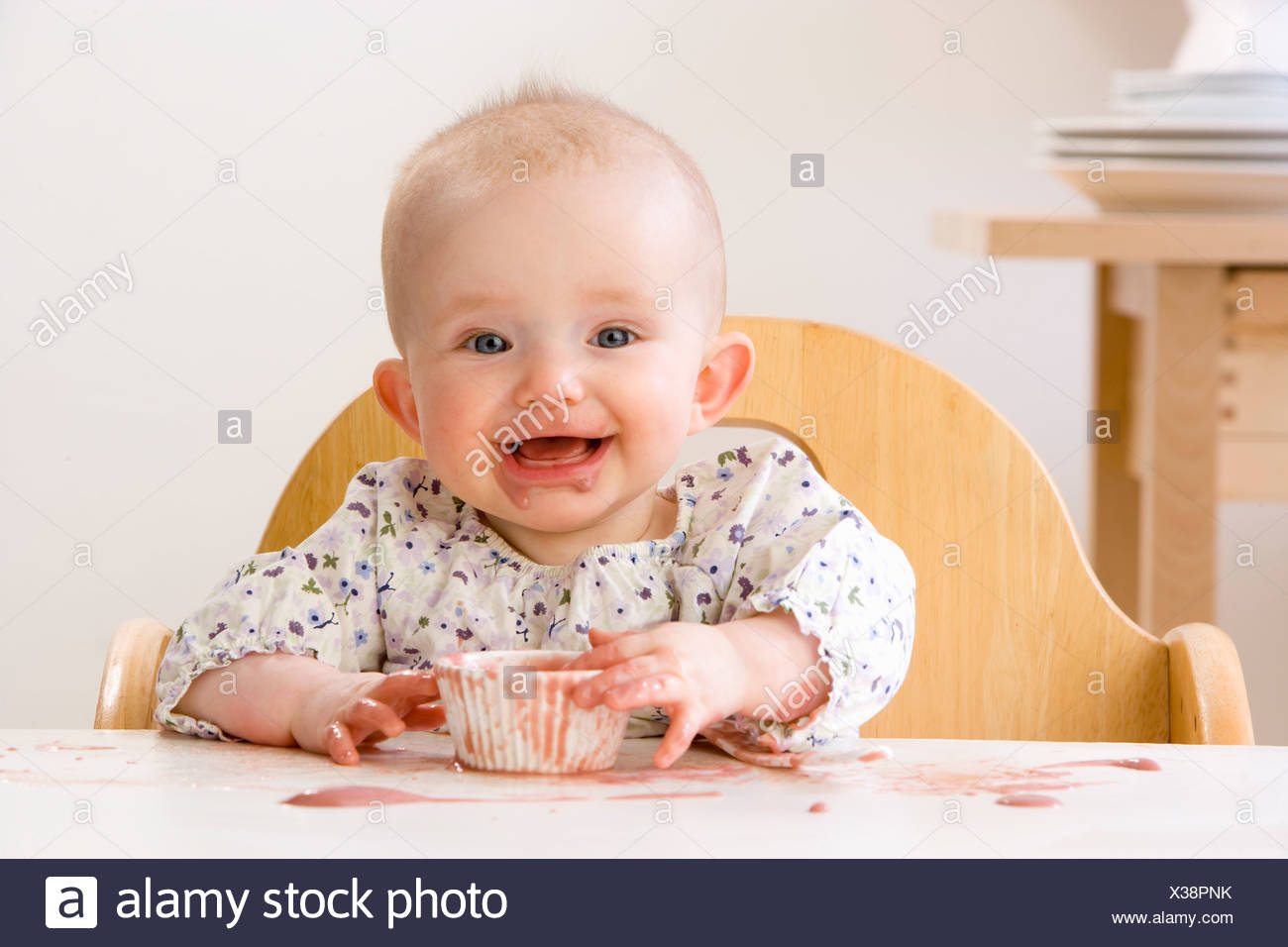 Messy baby girl in high chair eating - Stock Image