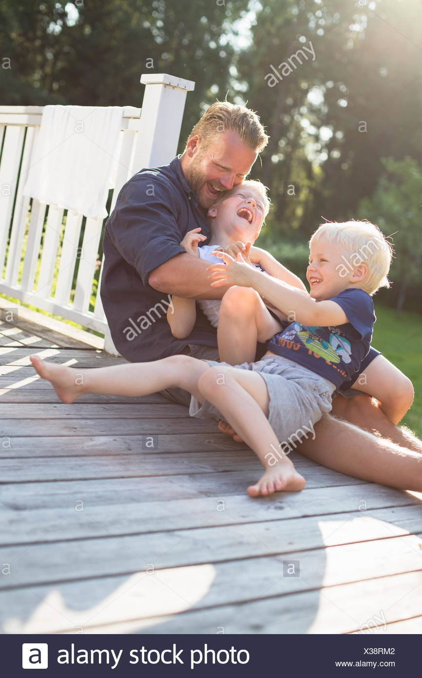 Sweden, Stockholm Archipelago, Grasko, Father playing with sons (4-5, 6-7) outdoors - Stock Image