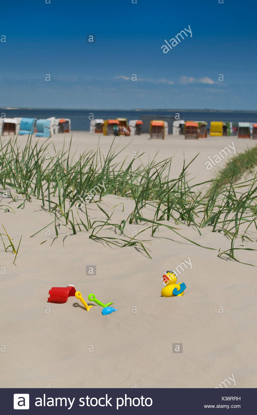 Colorful children's toys, bucket, spades and duck, in the sand on the beach of Norden, beach chairs against the blue sky at back - Stock Image