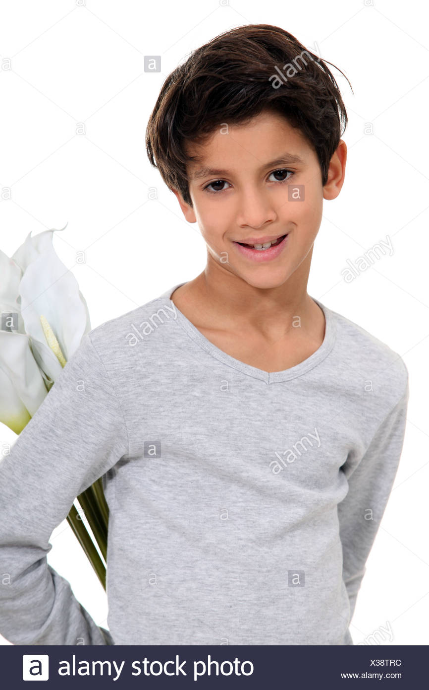 Little boy hiding a bunch of flowers in his back - Stock Image