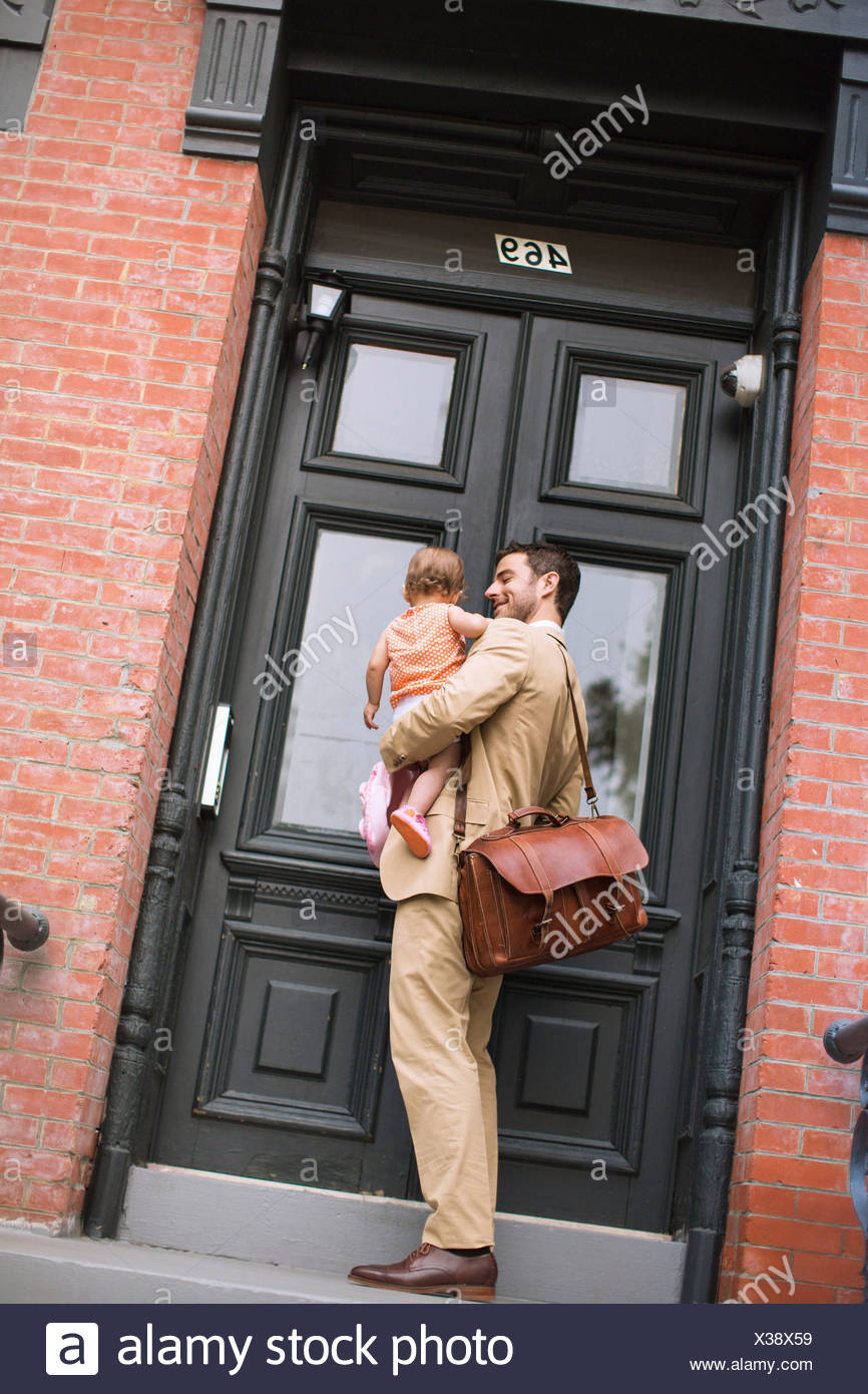 Man holding baby standing at front door - Stock Image