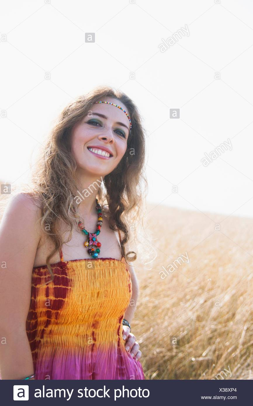 6e9c391a Portrait of mid adult woman wearing hippy clothes, standing in field ...