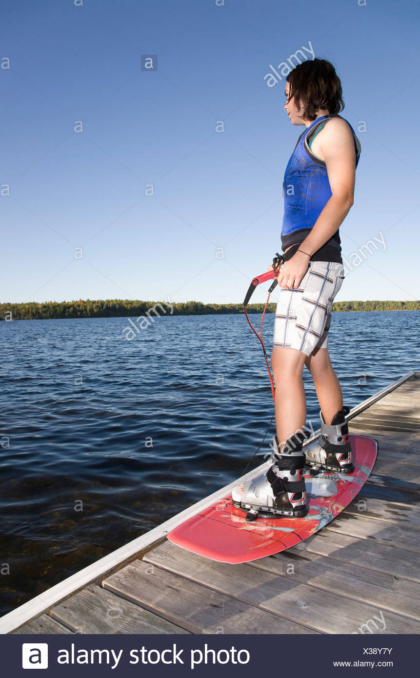 Woman standing on dock with wakeboard - Stock Image