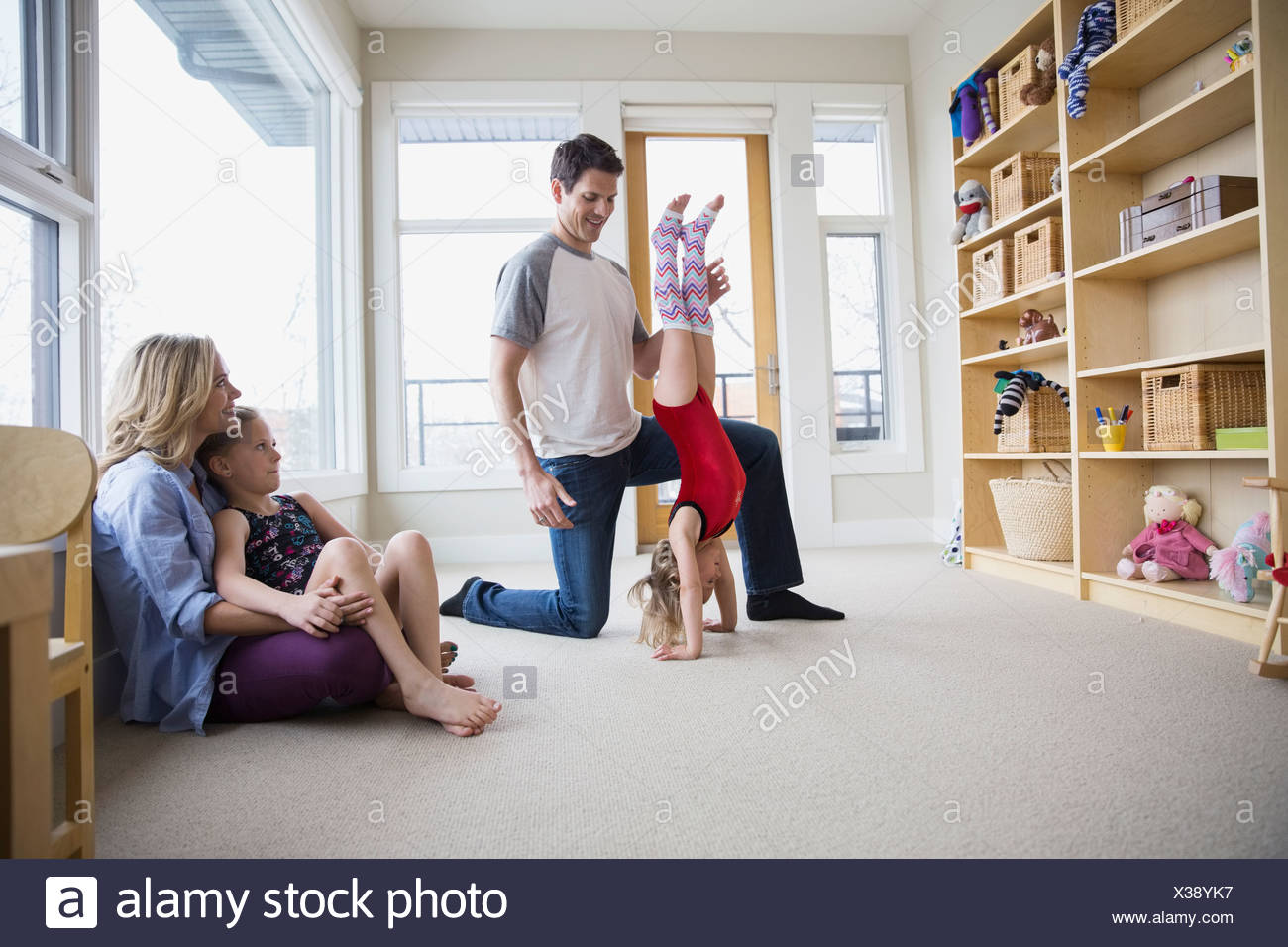 Father helping daughter do handstand in living room - Stock Image