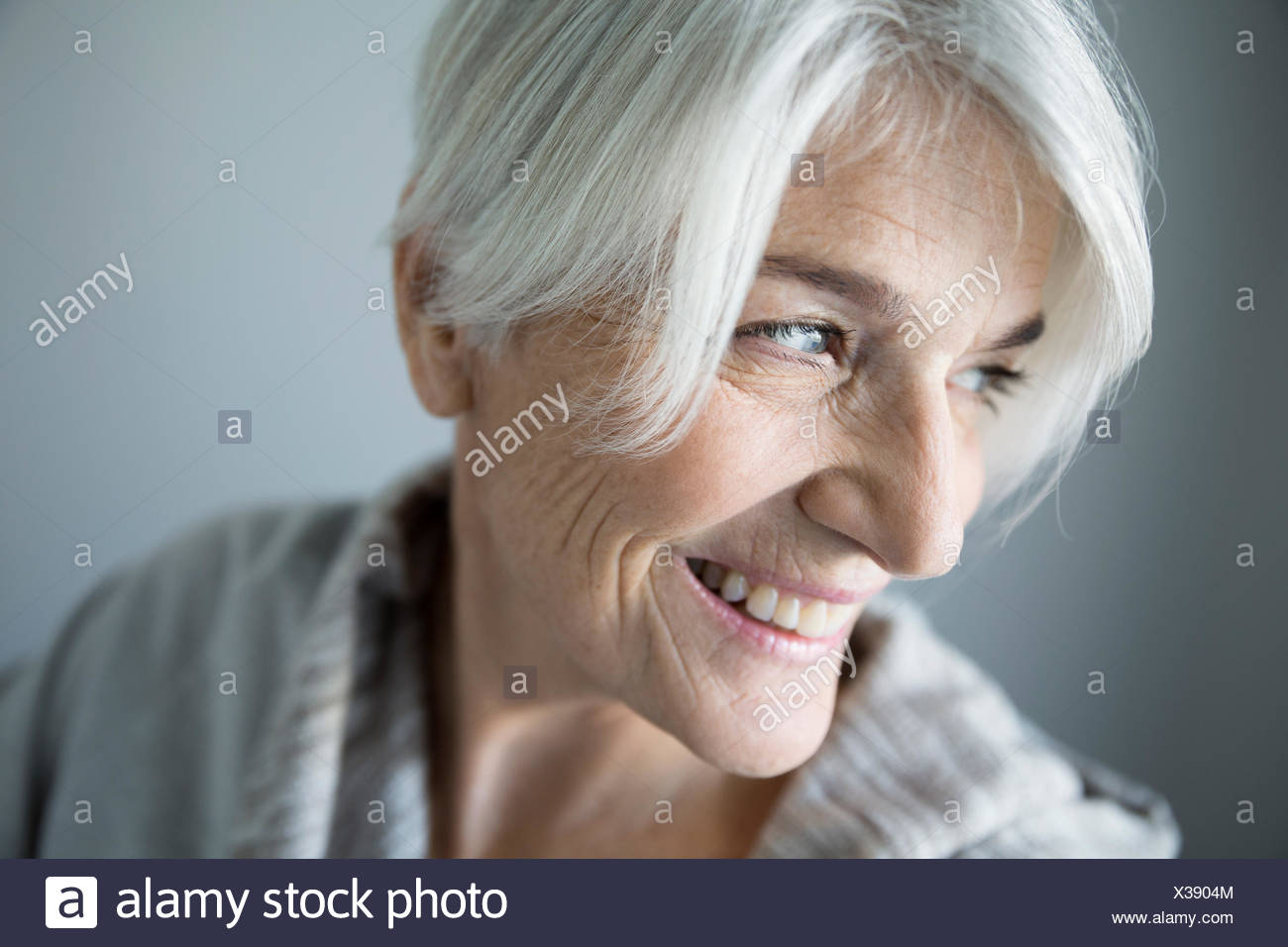 Close up smiling senior woman looking over shoulder - Stock Image