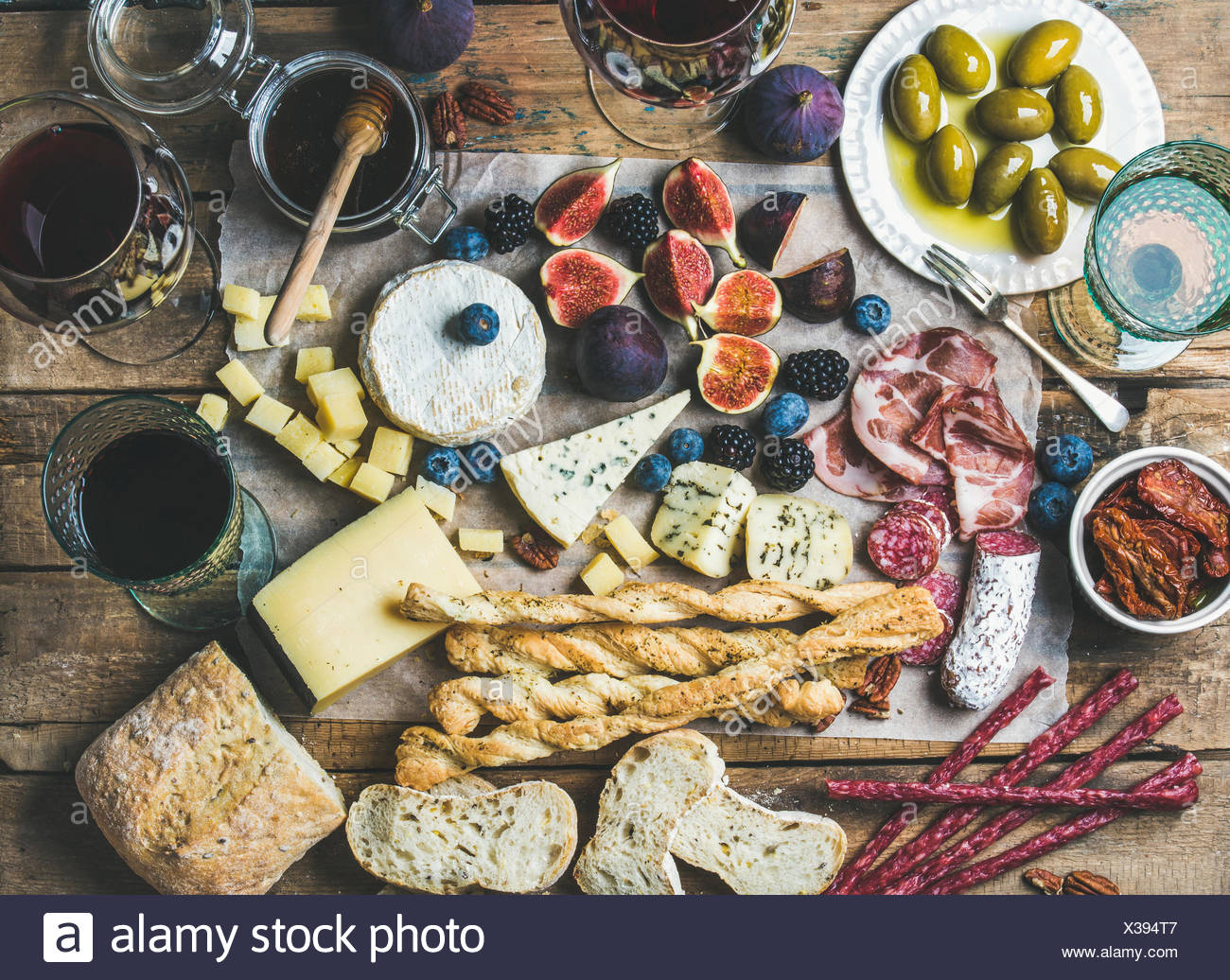 Wine and snack set with various wines in glasses, meat variety, ciabatta, sun-dried tomatoes, honey, green olives, figs, nuts an - Stock Image