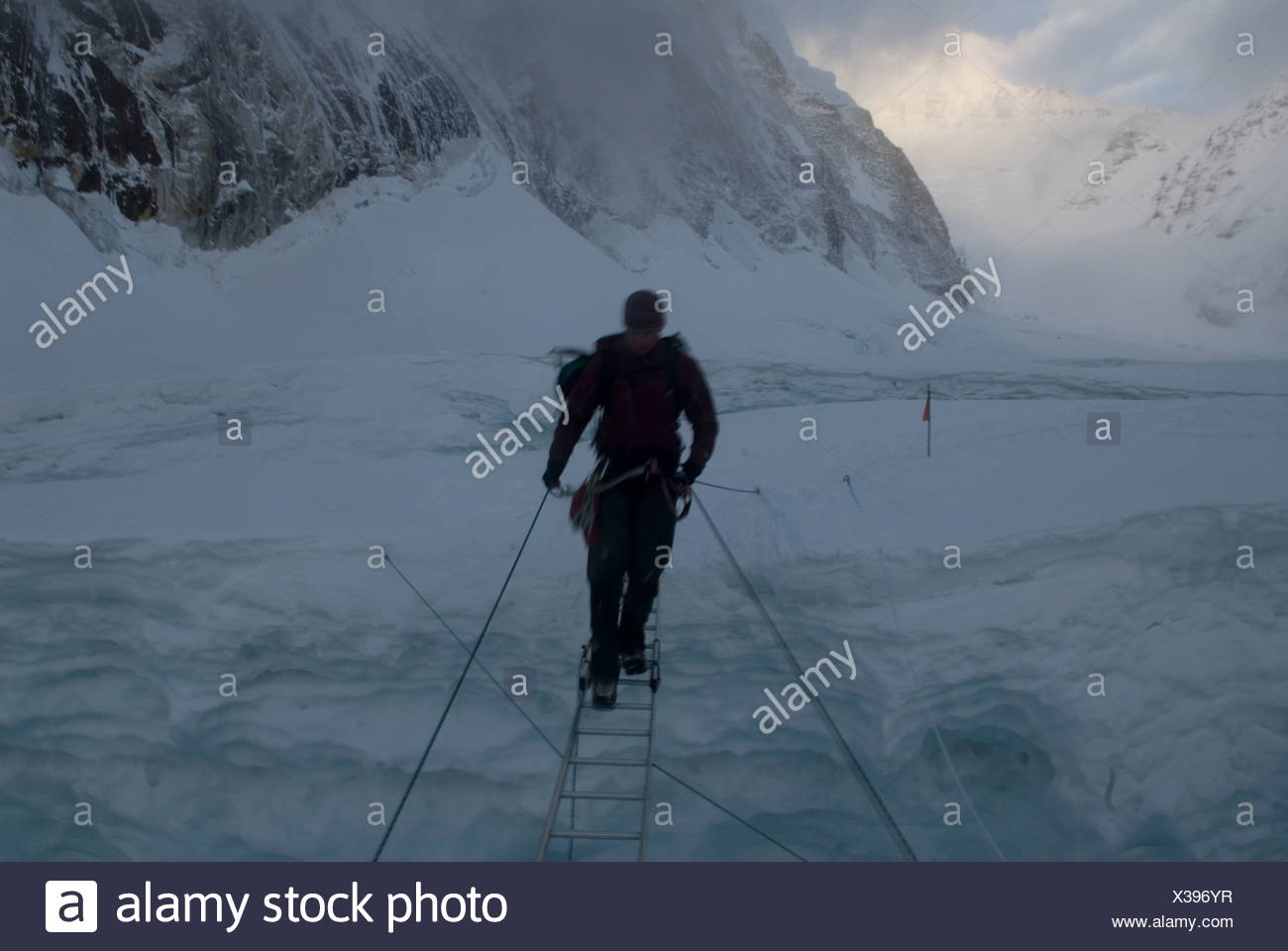 A climber crosses a crevasse, Everest's Khumbu Icefall, Nepal. - Stock Image
