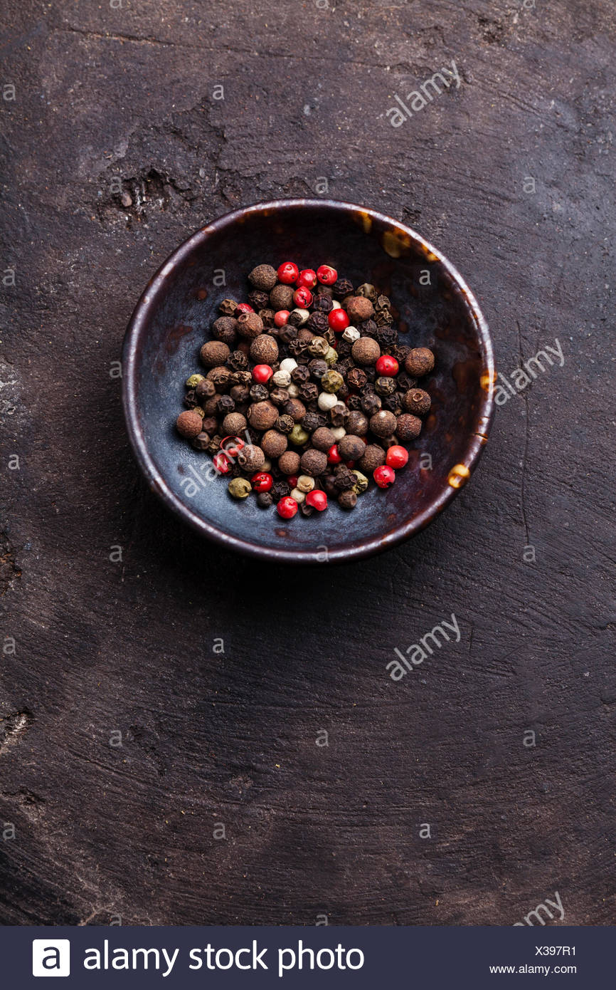 Multicolored peppers peas on dark background - Stock Image