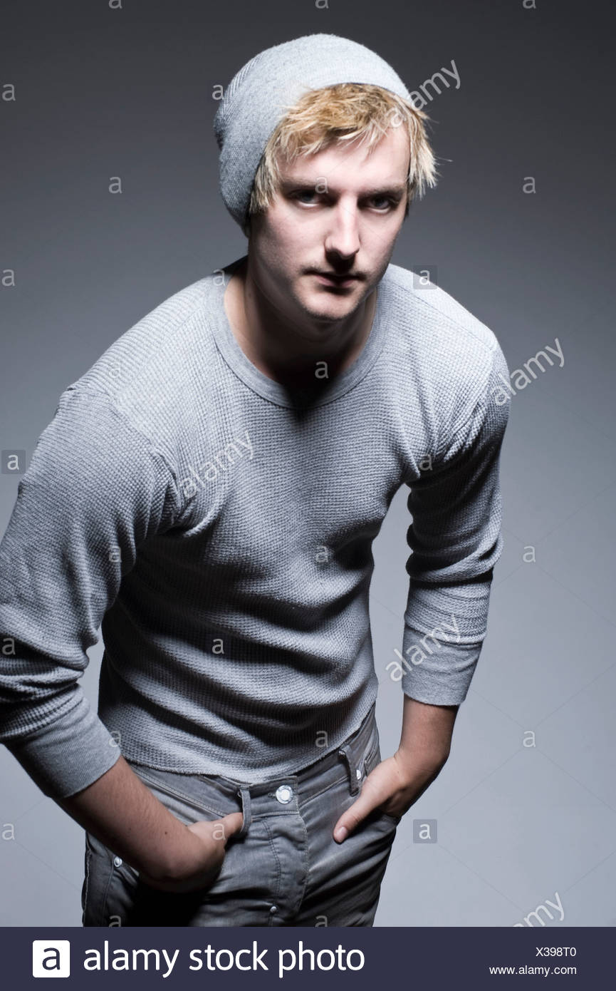 Young man in grey sweatshirt with hands in pockets, portrait - Stock Image