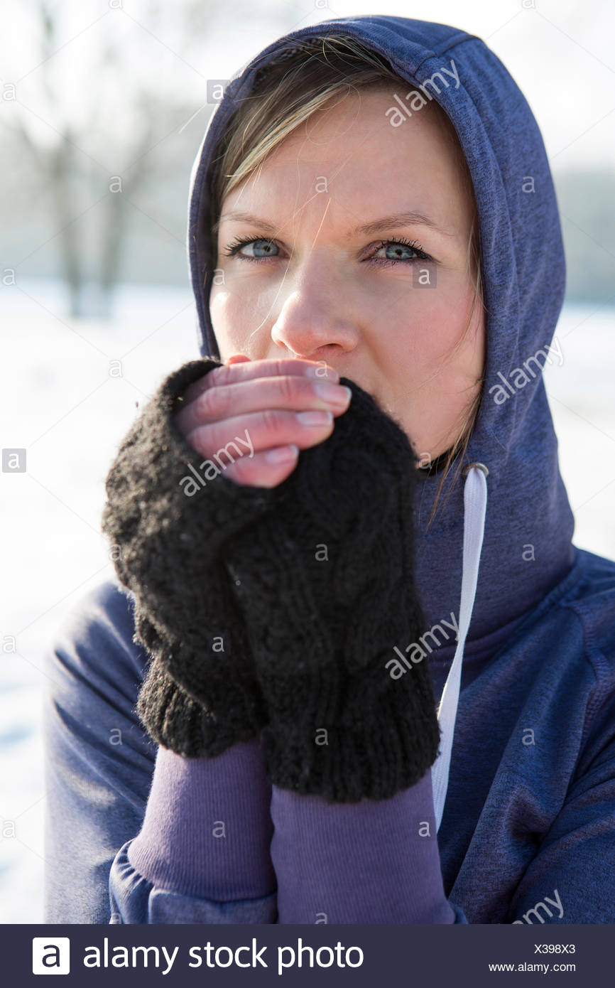 Woman in hooded shirt feeling cold - Stock Image