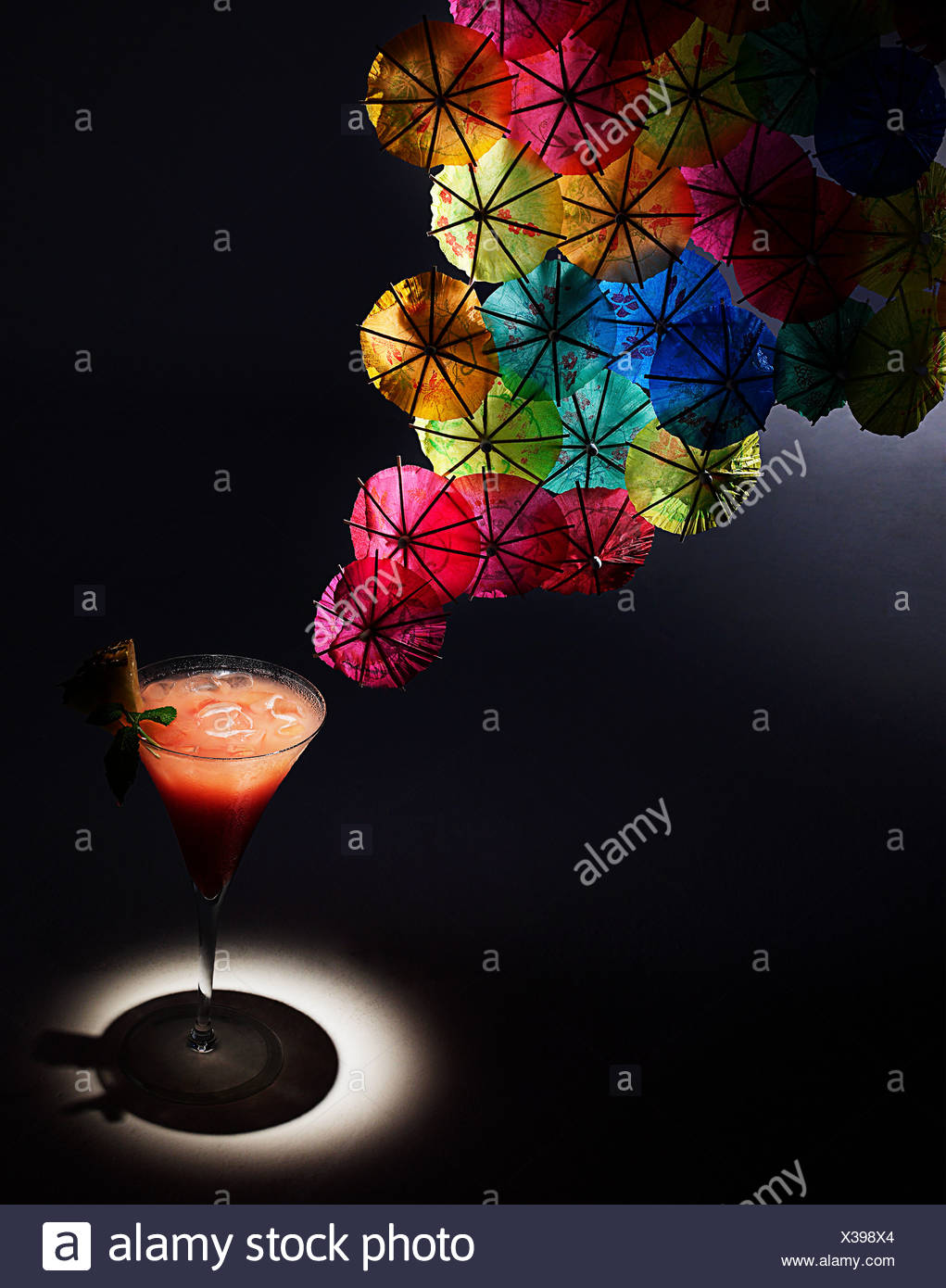Cocktail and colourful cocktail umbrellas, studio shot - Stock Image
