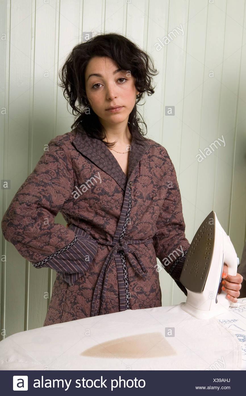A woman holding an iron next to a burnt shirt - Stock Image