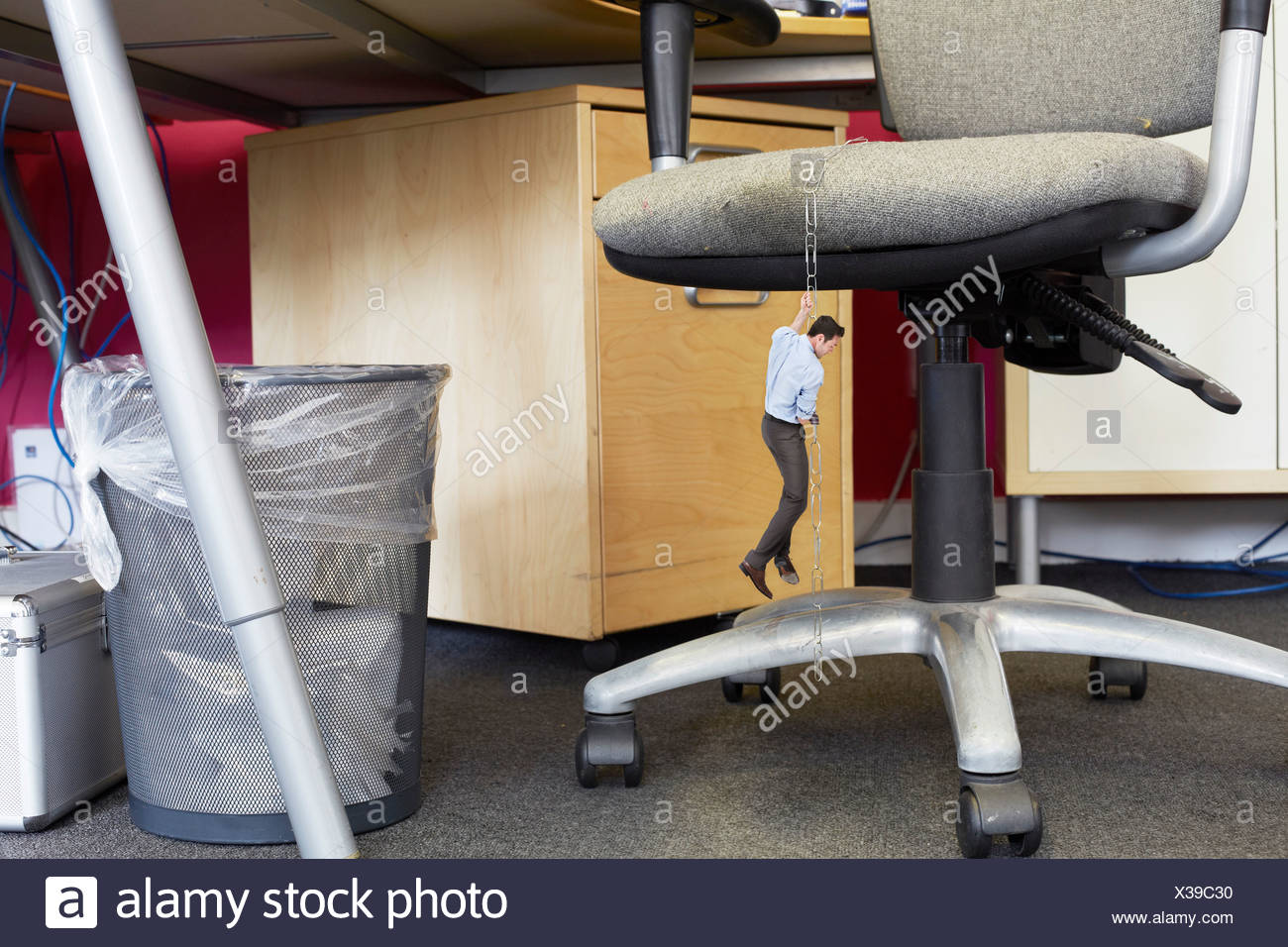 Businessman climbing down large paper clips on oversized office chair - Stock Image