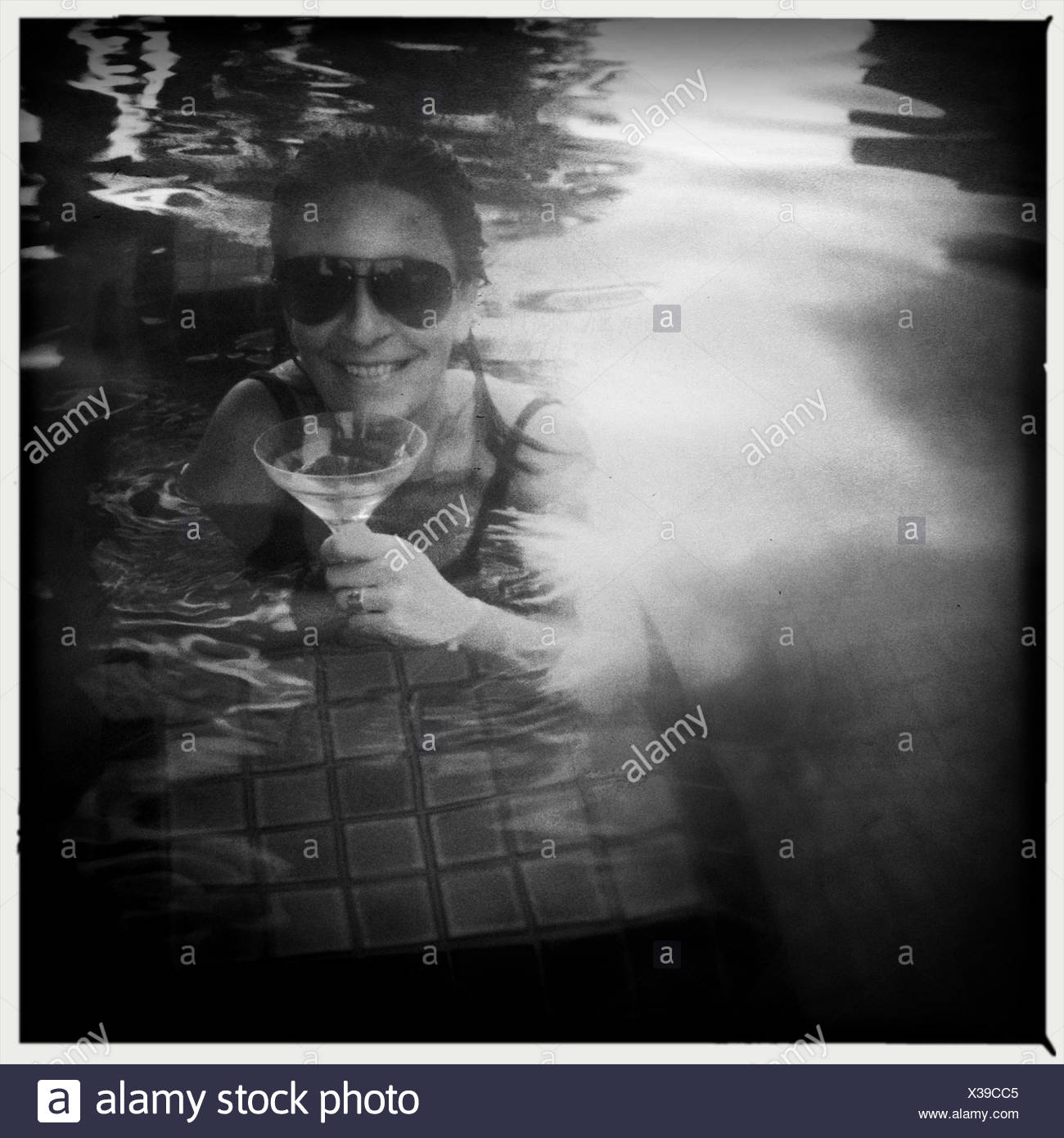 Woman drinking cocktail in swimming pool - Stock Image