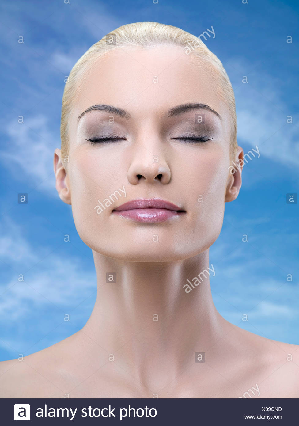 Portrait young adult woman with eyes closed, studio shot - Stock Image