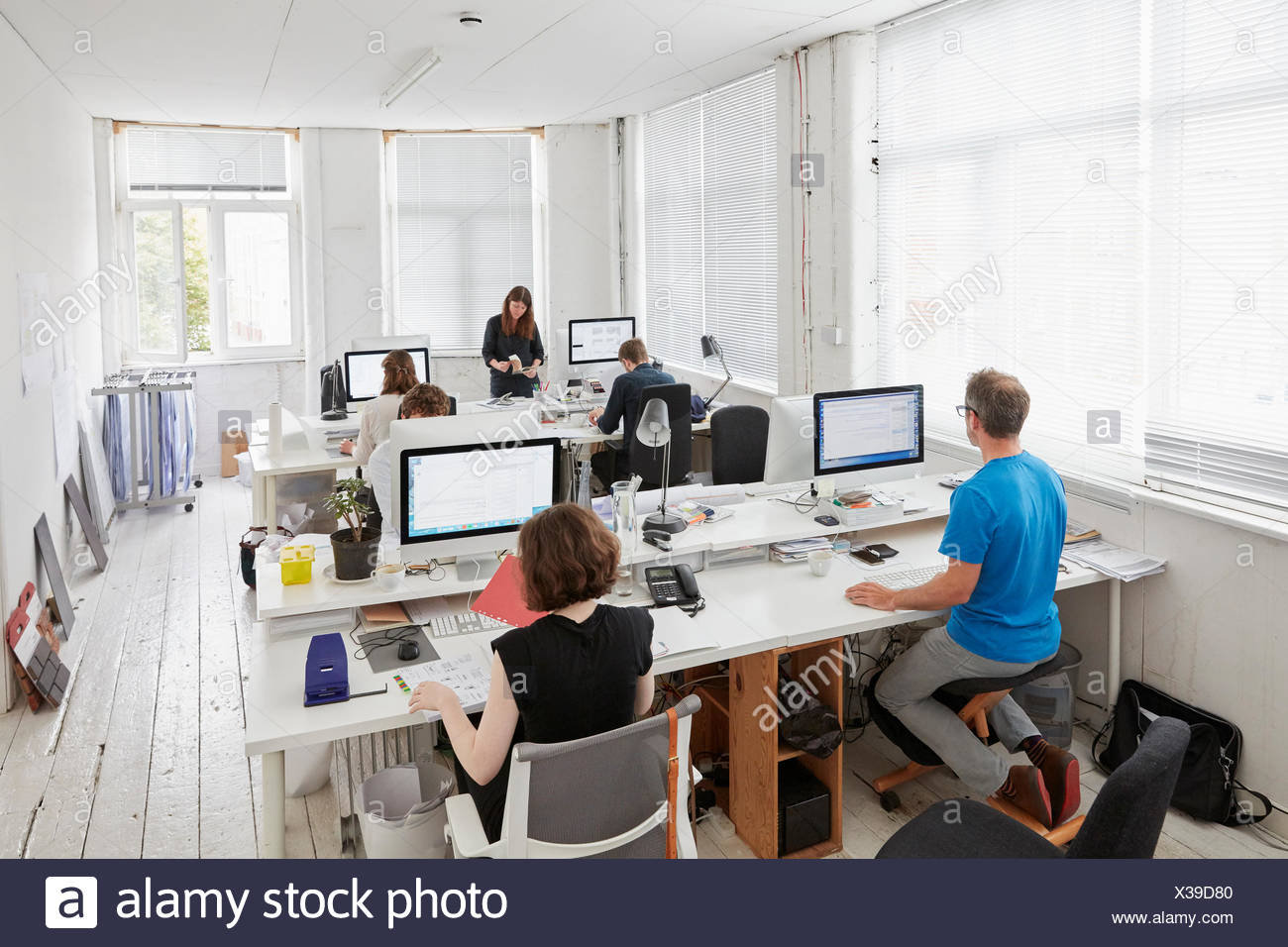 A modern office, workstations for staff. Elevated view of six people seated at desks. A man using an ergonomic kneeler chair. - Stock Image