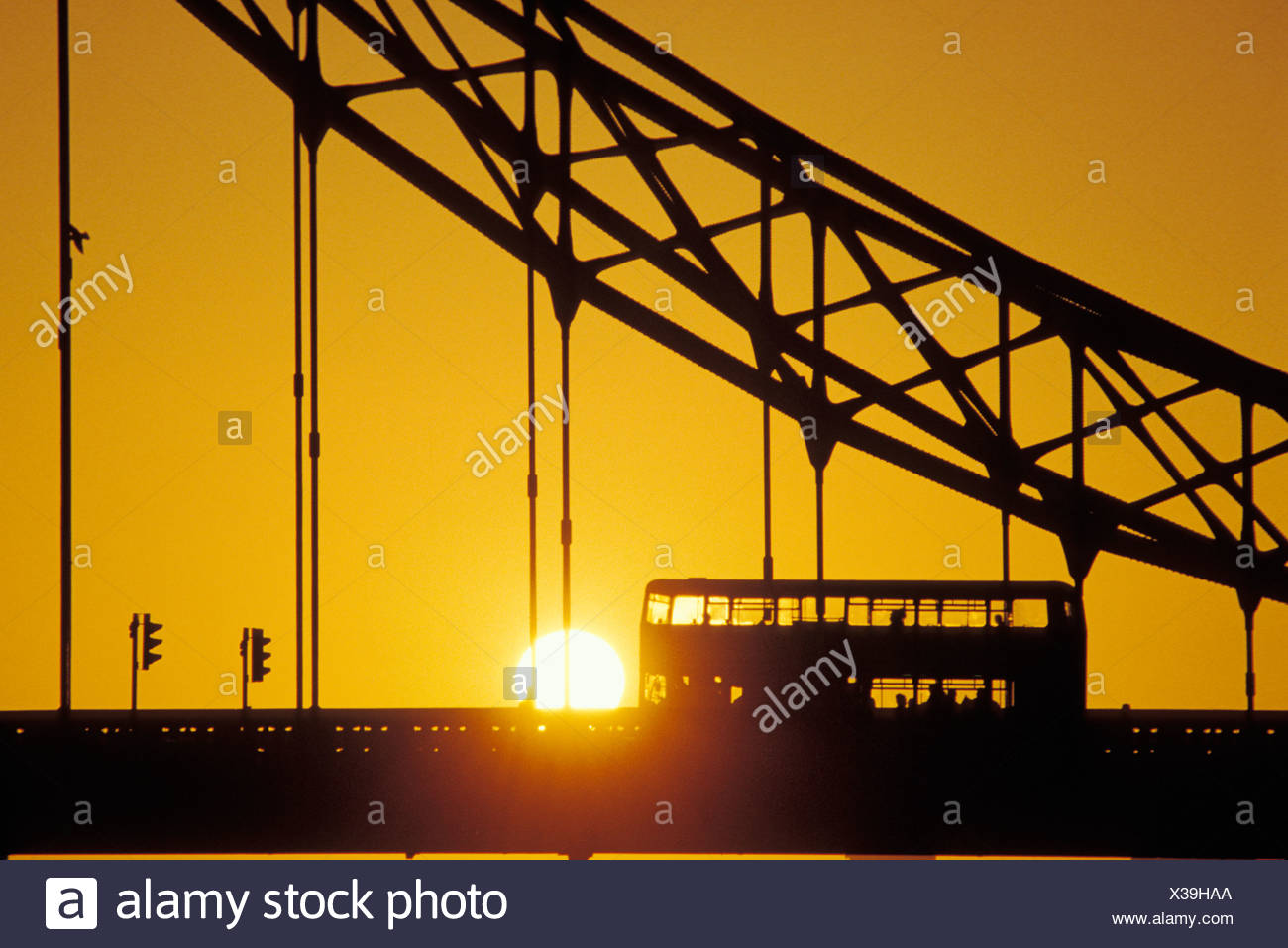 Silhouette of suspension bridge and double decker bus with sunset in background - Stock Image