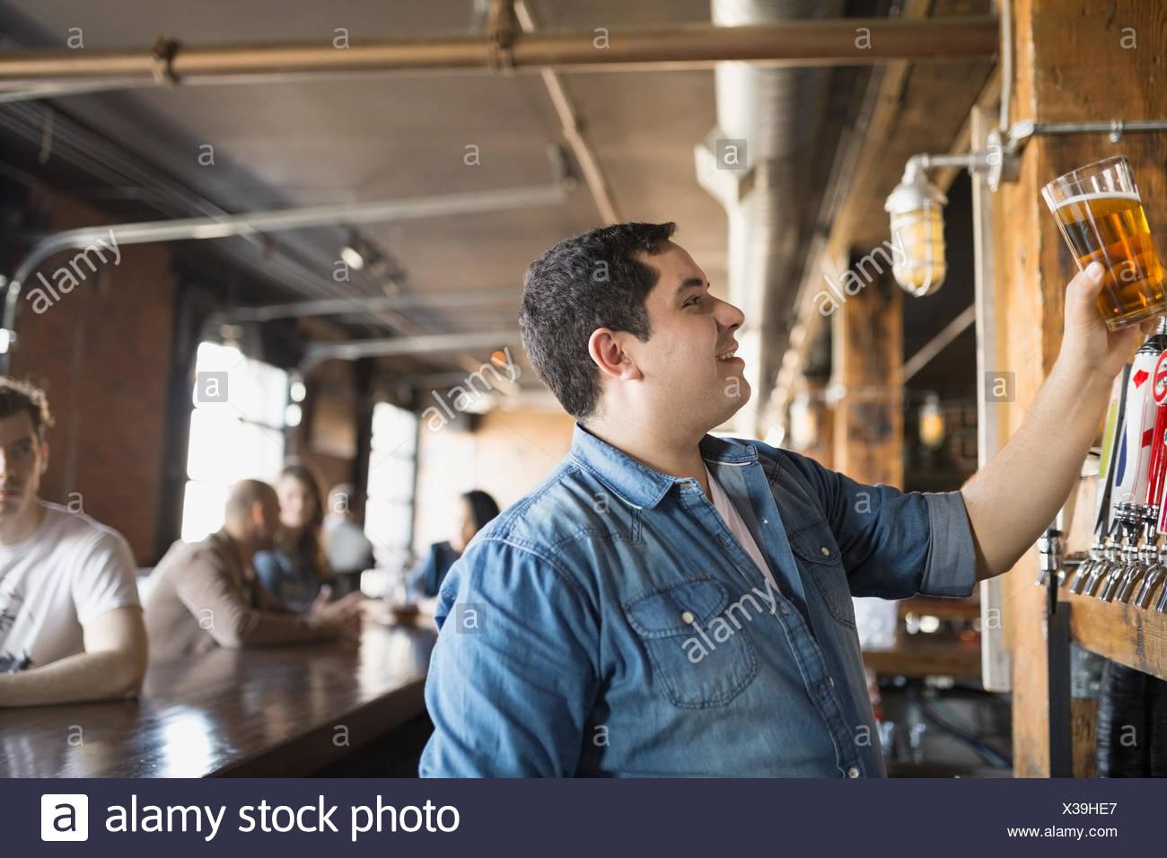 Bartender eyeing pint of beer - Stock Image