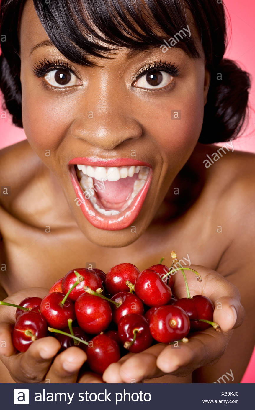 Portrait of woman with hands full of cherries Stock Photo