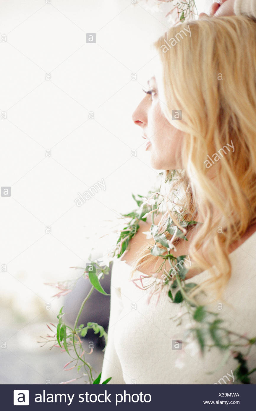 Head and shoulders portrait of a blonde woman, a creeper plant wrapped around her body. - Stock Image