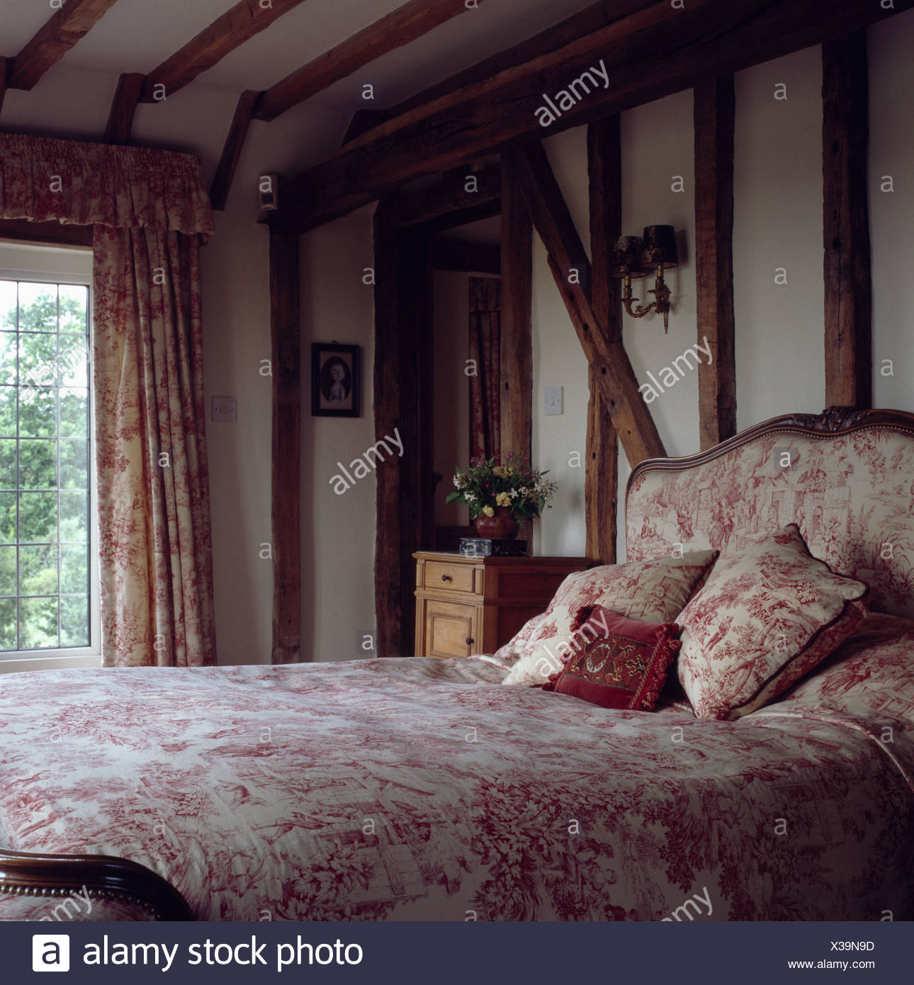 Pink Bedroom With Beamed Walls And Bed With Upholstered Headboard And Pink Bedlinen Stock Photo Alamy