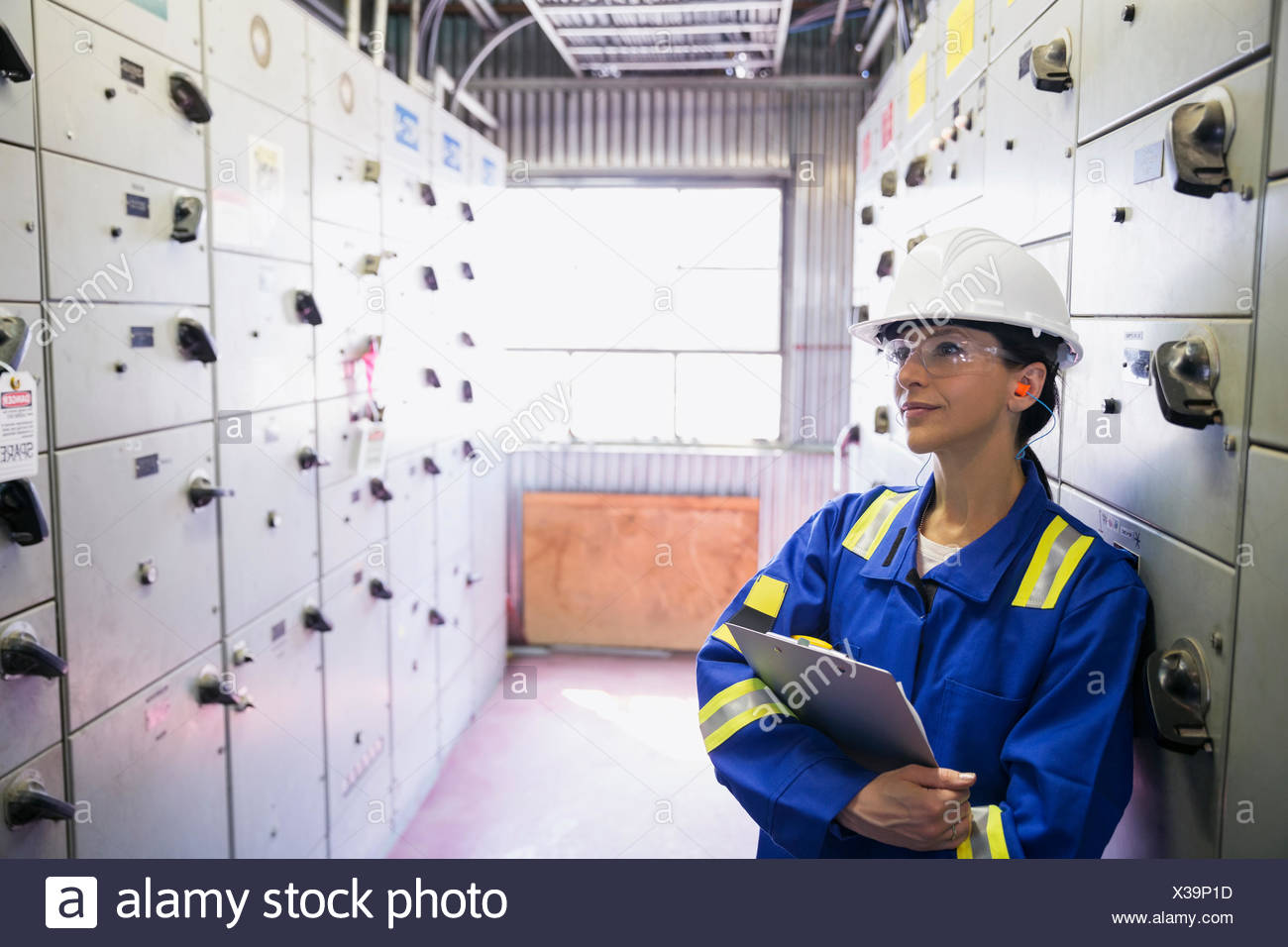 Pensive female worker in gas plant - Stock Image