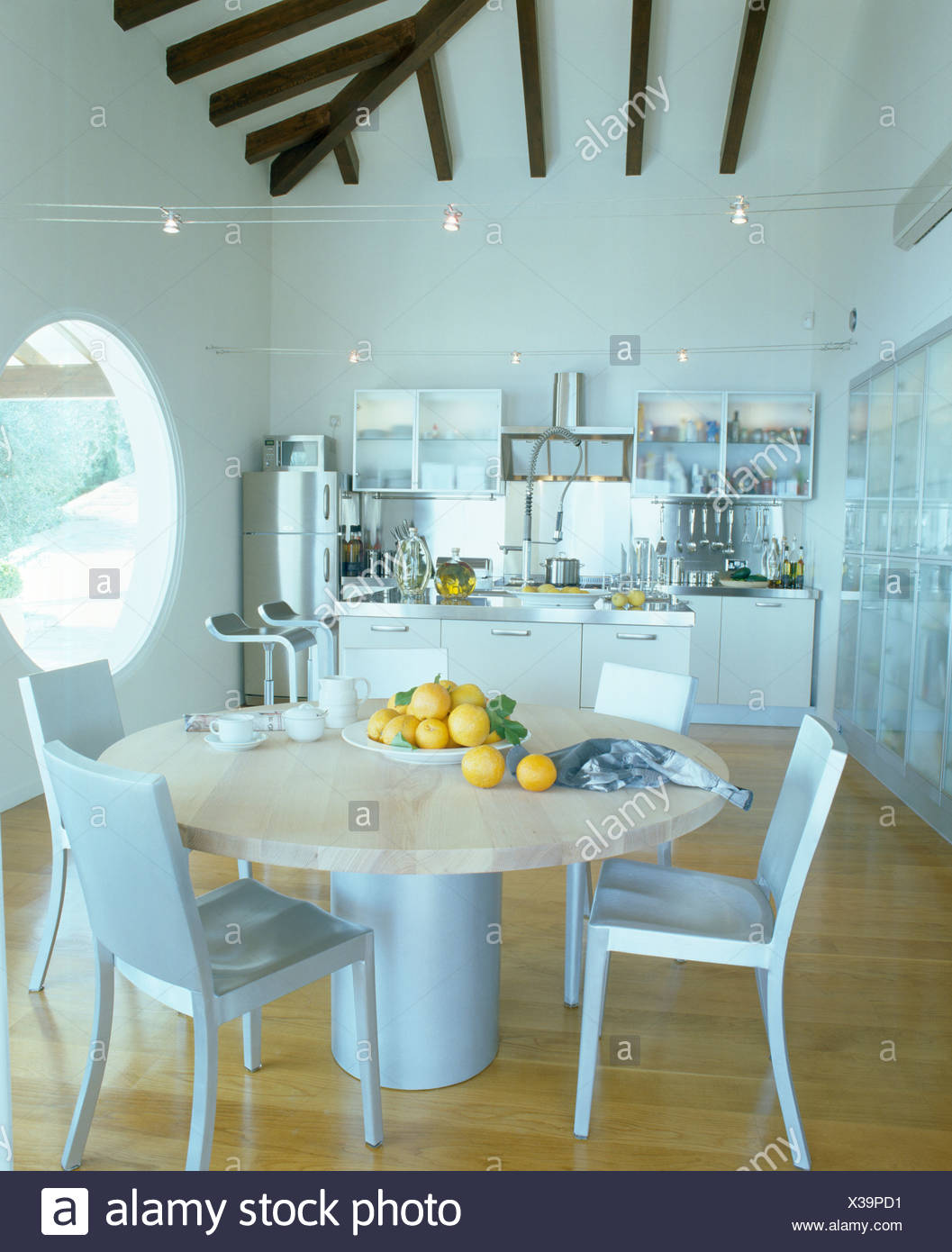 Metal chairs and circular marble table in modern white Mediterranean ...