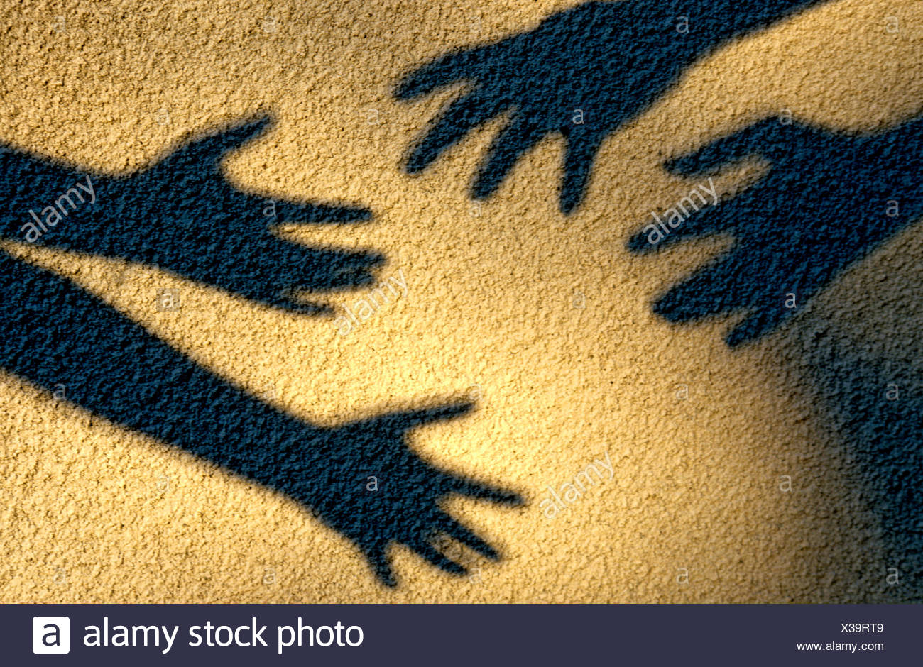 Shadows of hands reaching to touch each other - Stock Image