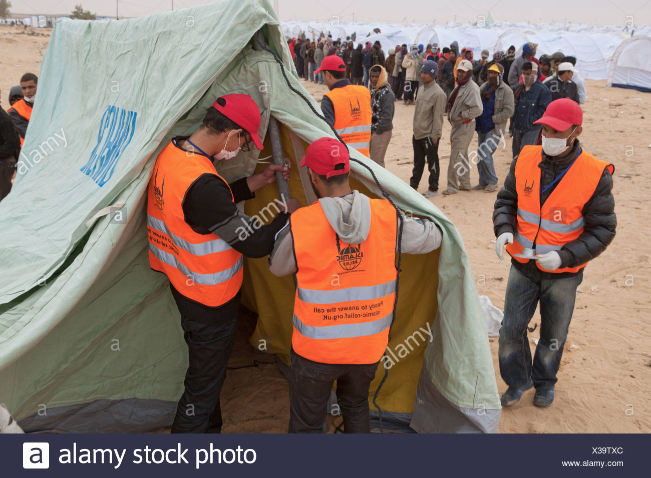 Members of the aid organisation Islamic Relief pitching a tent, Ben Gardane, Tunisia - Stock Image