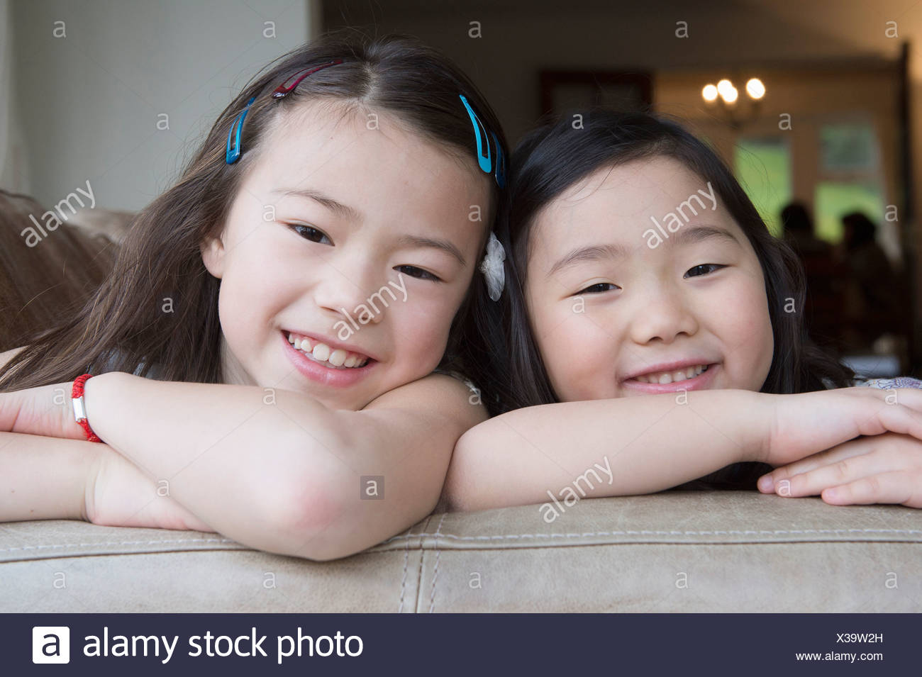 Portrait of two young girls leaning on sofa Stock Photo